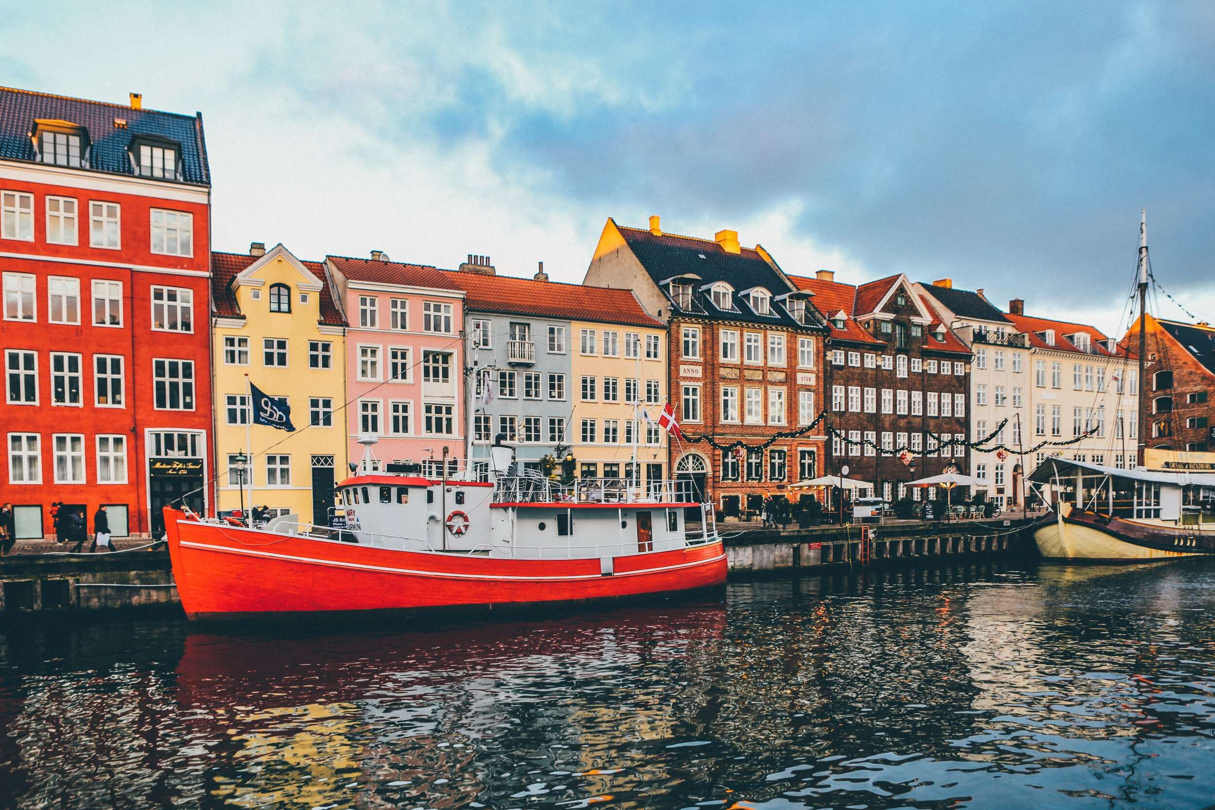 colourful houses and boats in the harbour in nyhavn copenhagen, denmark