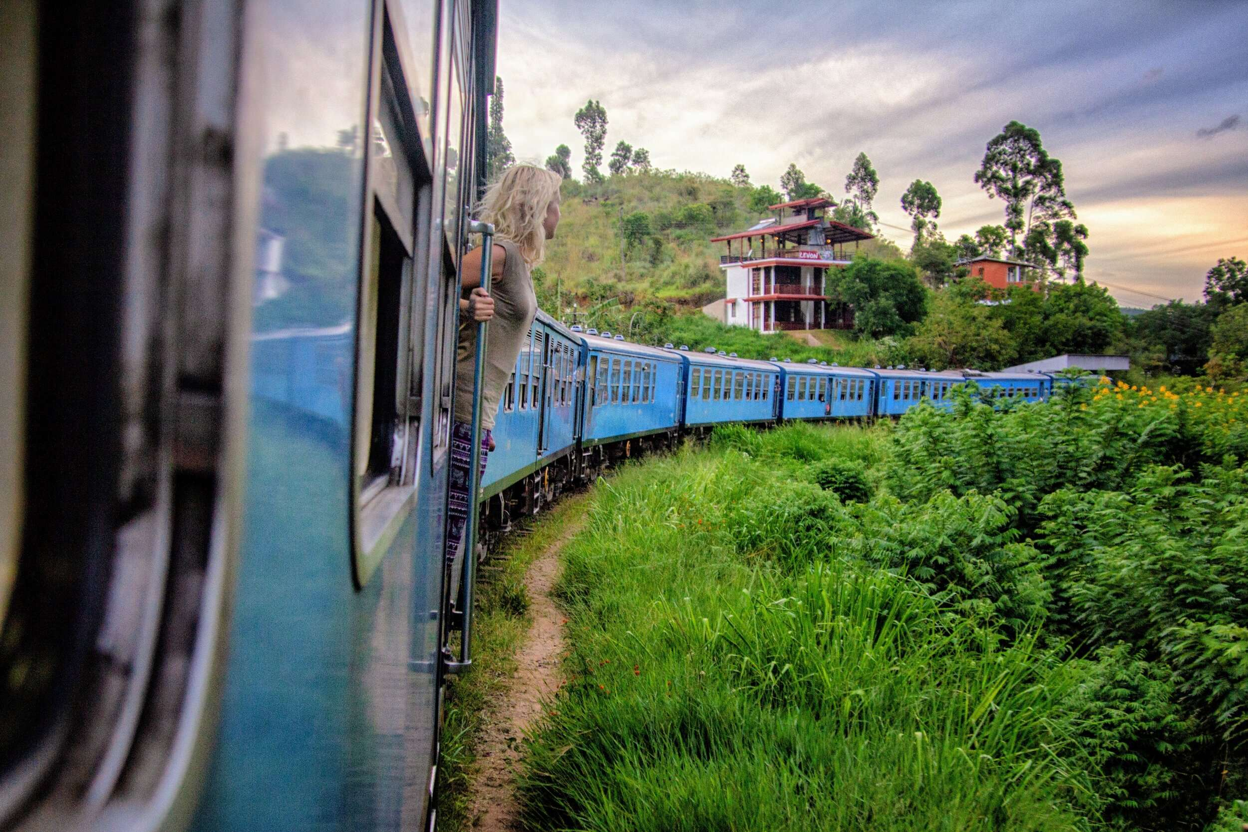 Wonan leans outside a passenger train in Ella, Sri Lanka