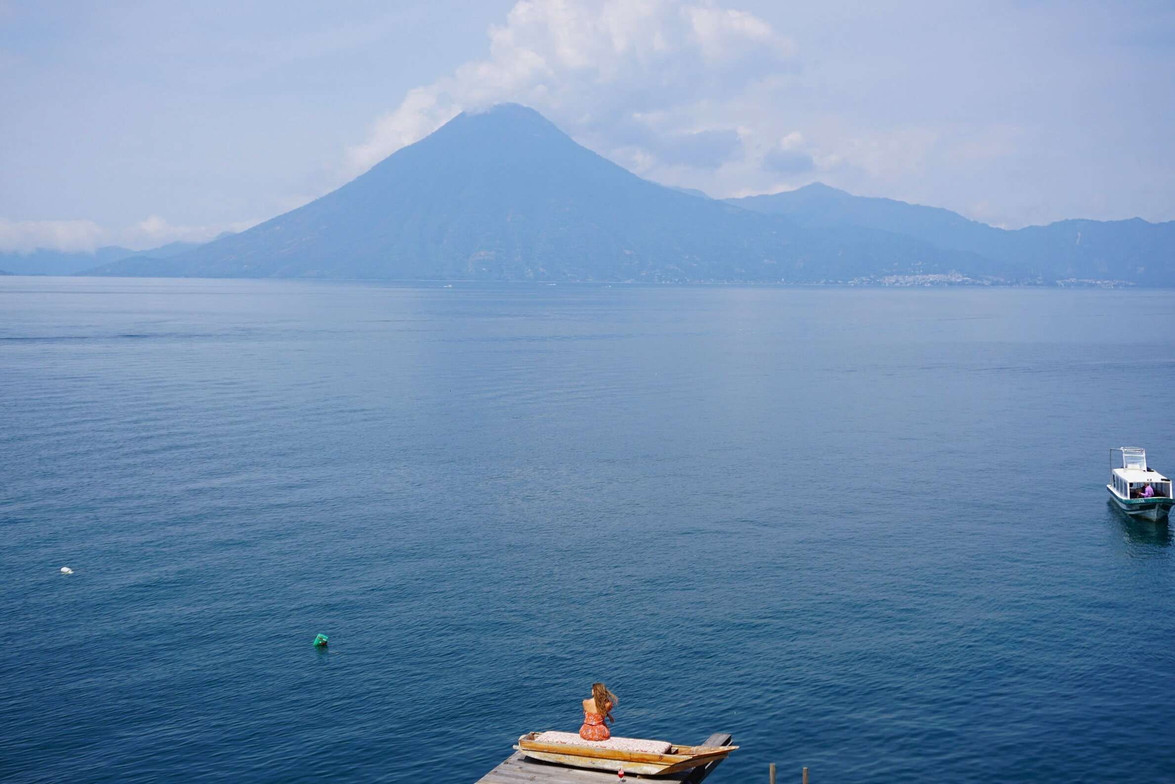 Woman sits on a dock of Laguna Lodge overlooking Lake Atitlan in Guatemala