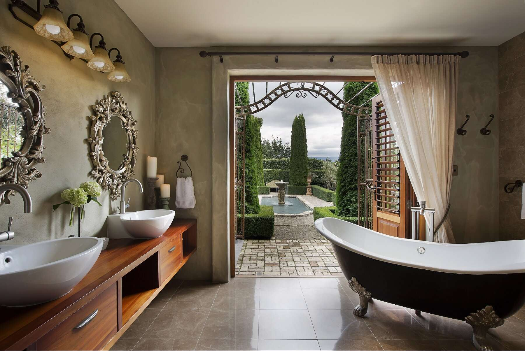 elegant bathroom with black and white freestanding bathtub with a view through open patio doors looking into the pristine garden with water feature