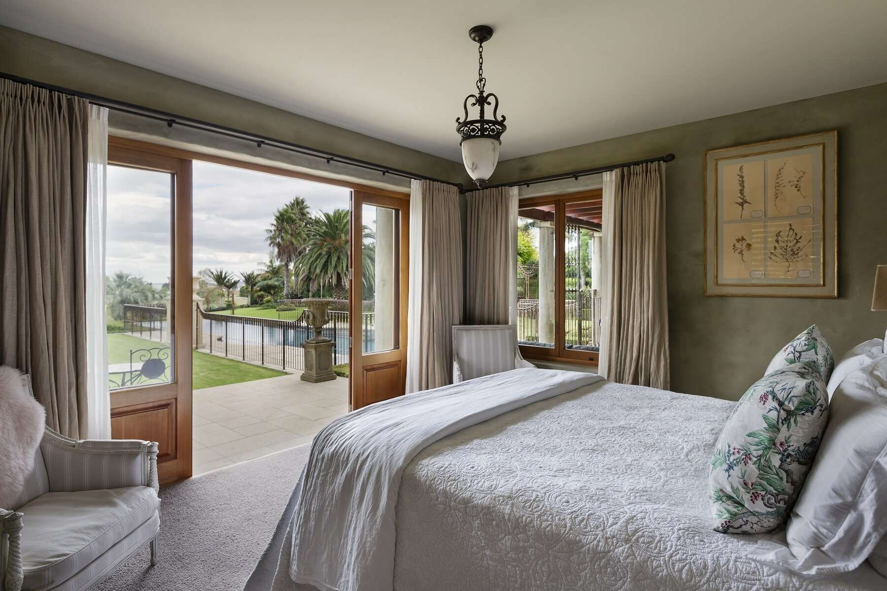 bedroom at Ataahua Lodge with open doors leading out to the garden and pool