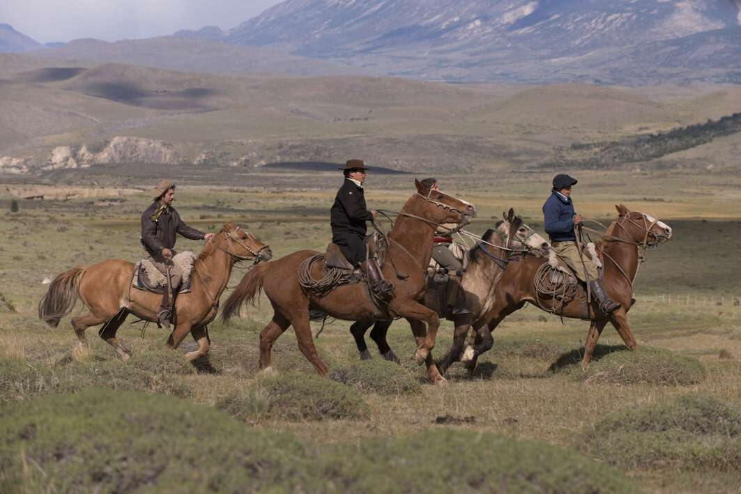 med ride horses through open fields in Patagonia