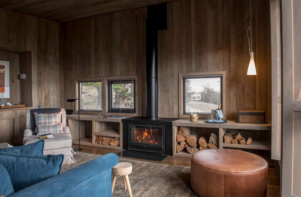 inside a wooden cabin with log fire burning, at Awasi Patagonia, one of the best villas in the world