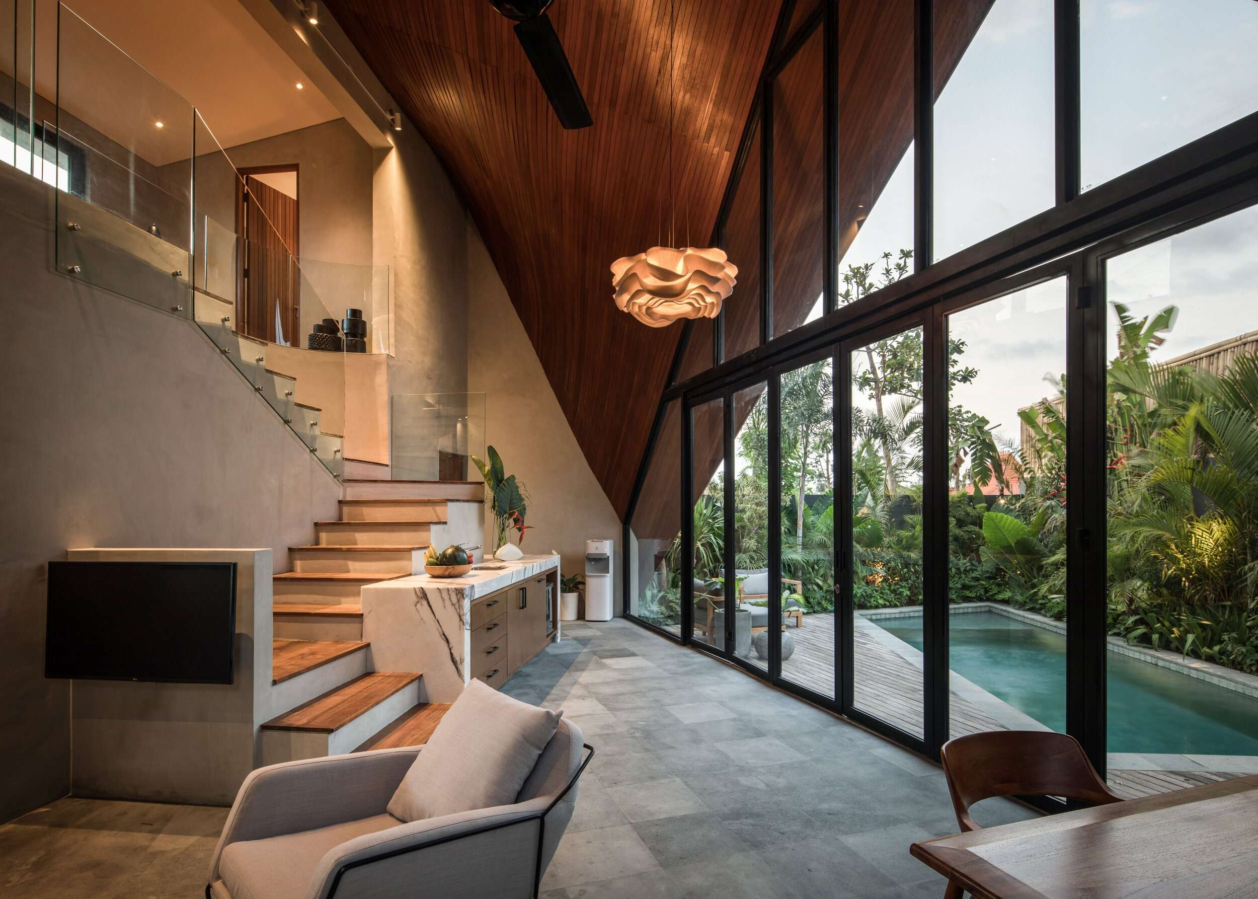 wooden staircase in the centre of a living space with high ceilings and a glass wall with swimming pool outside, at Riverhouse Bali