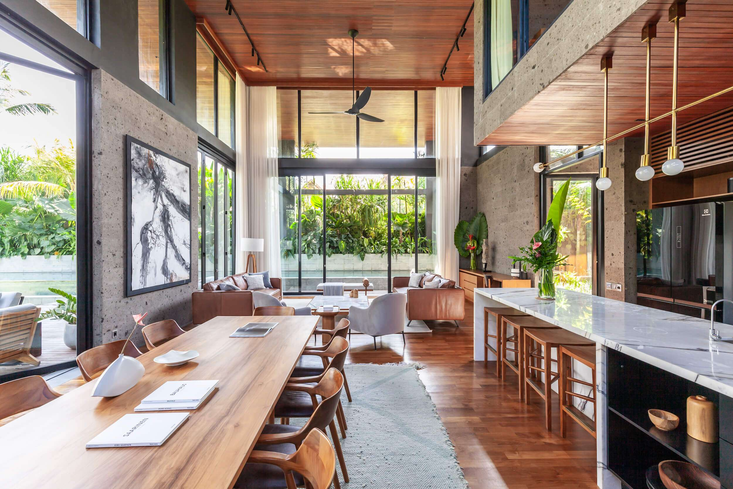 Long wooden dining table in the living area at Riverhouse Bali, one of the best villas in the world