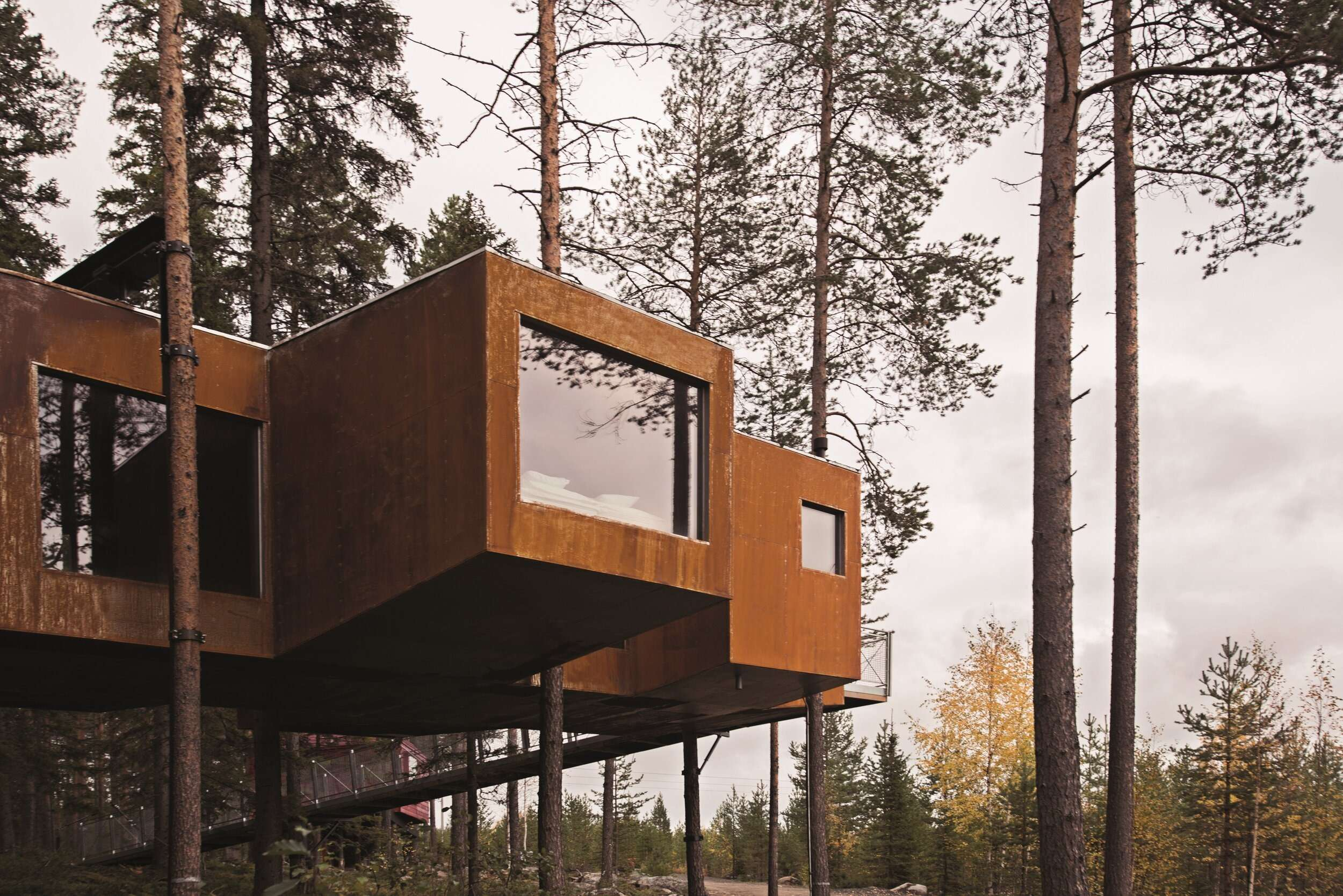 two brown containers suspended on vertical beams amongst trees at Treehotel