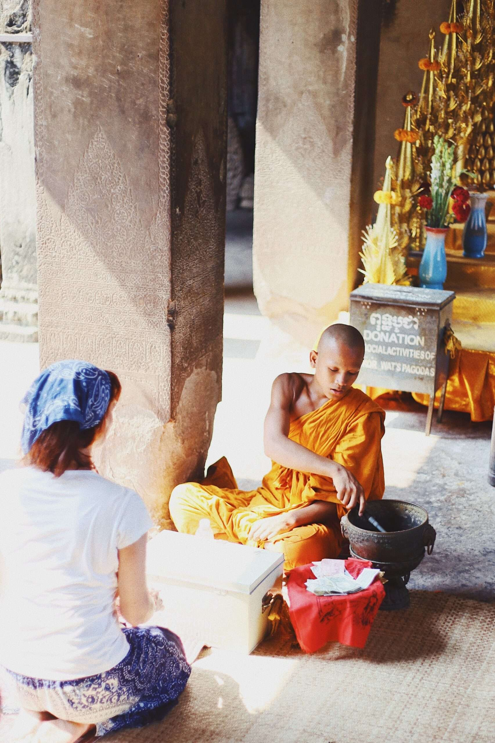 young monk blesses a female tourist inside the temples during a visit to Angkor Wat