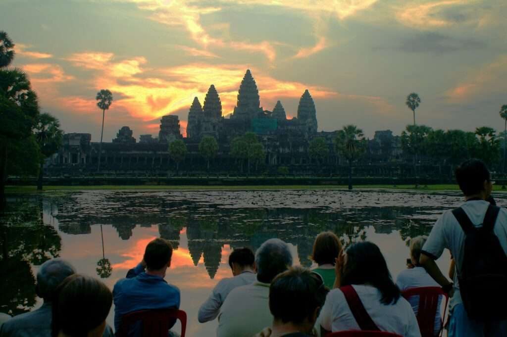 people watching the sunrise over Angkor Wat across the water, the silhouette reflecting in the water
