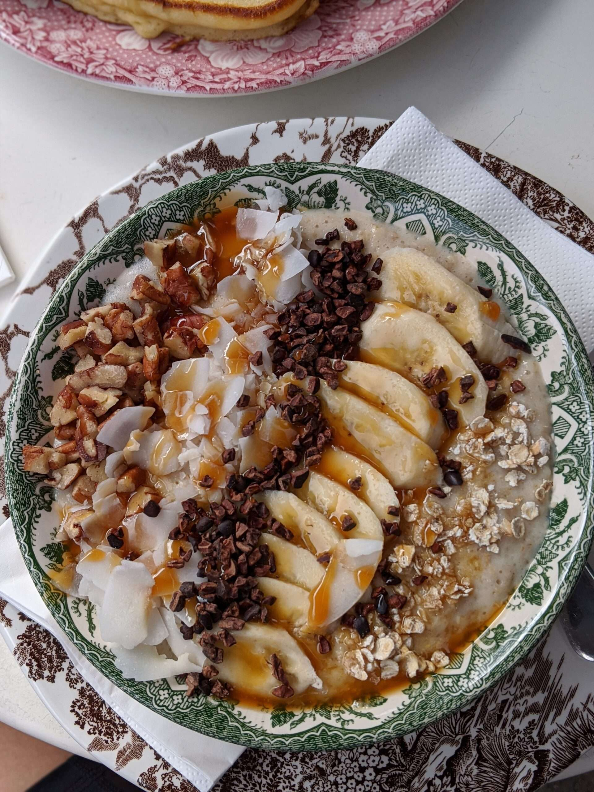 oatmeal topped with sliced banana, cacao nibs, shredded coconut and chopped nuts presented in a green and white painted bowl