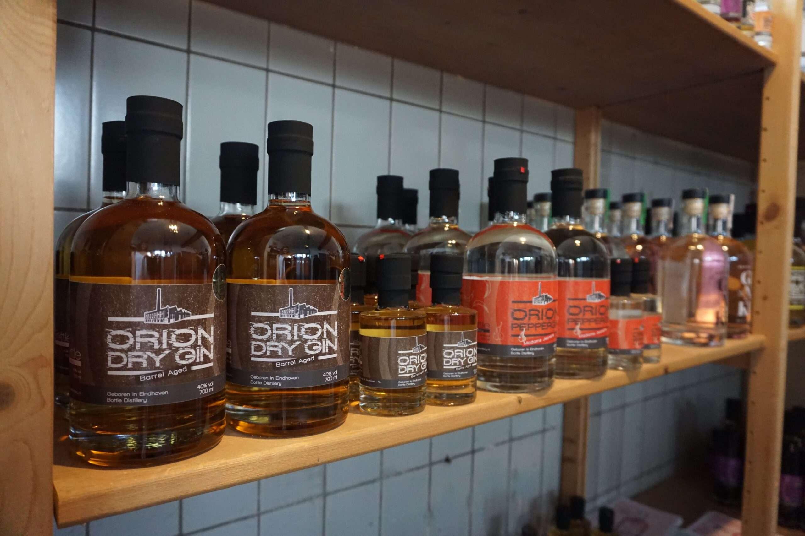 wooden shelf displaying rows of bottled gin at Bottle Distillery Eindhoven