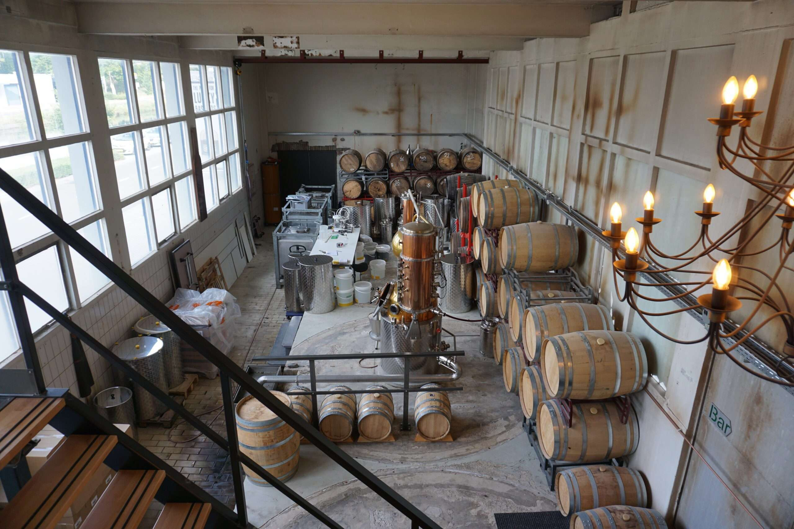 Distillery room with large wooden barrels lined up against the wall and shiny distilling equipment in the centre of the room at Bottle Distillery Eindhoven