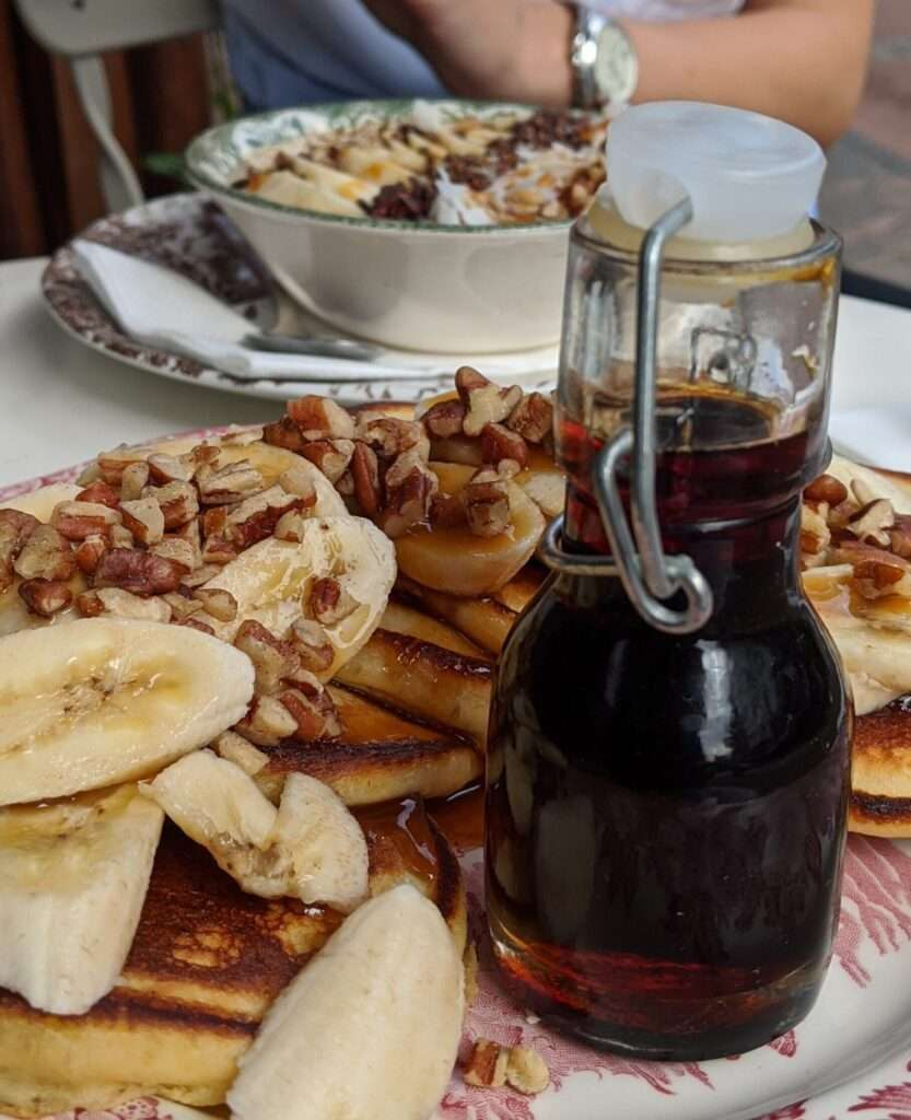 small glass bottle of syrup on a plate with pancakes topped with banana slices and chopped walnuts
