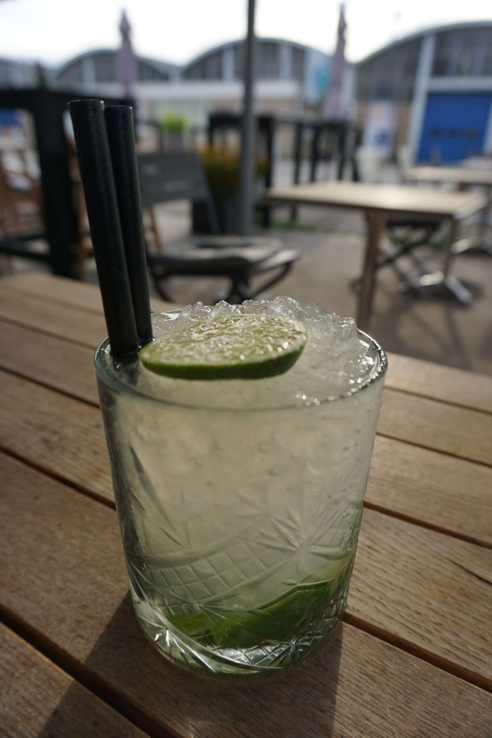 crystal glass with mojito cocktail topped with lime wedge and 2 black straws, on a wooden table at Bottle Distillery Eindhoven