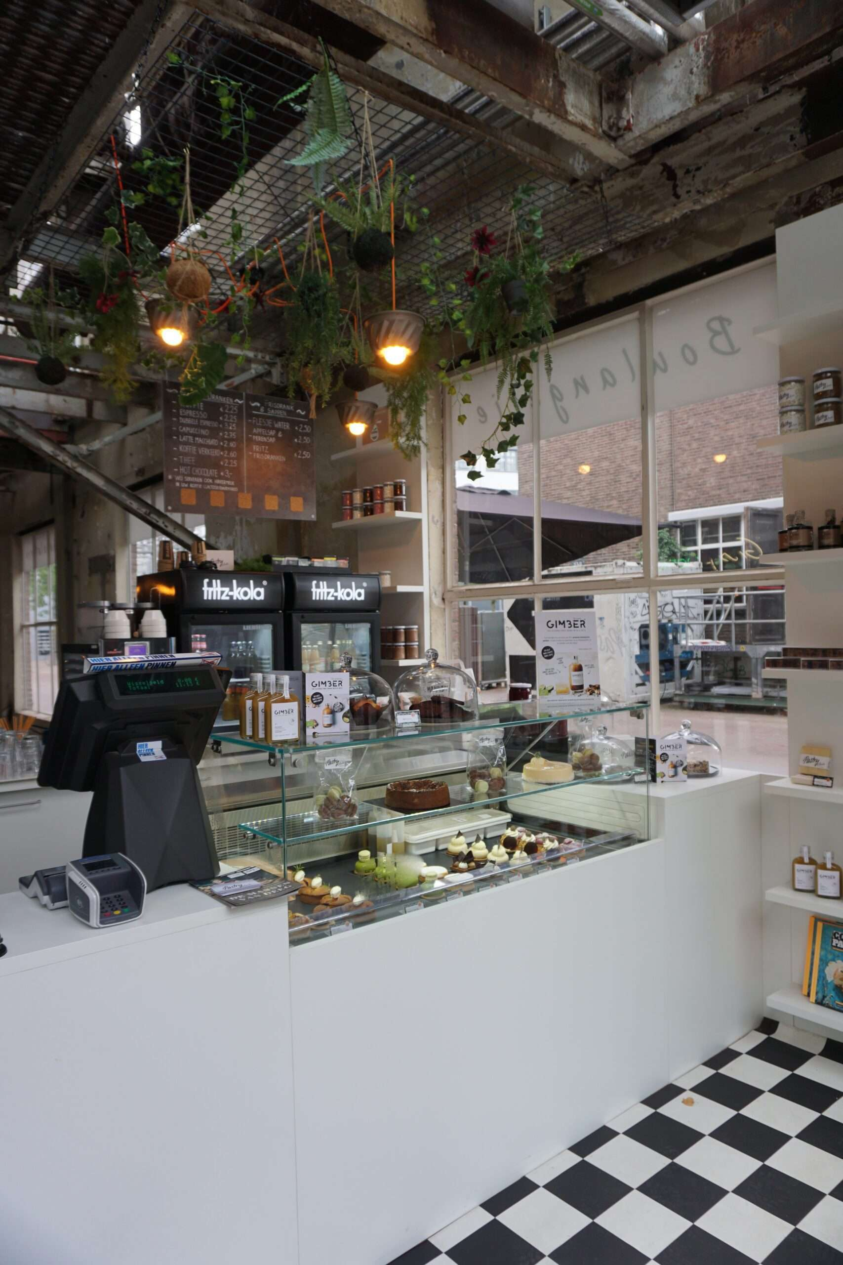 Inside Pastry Club in Eindhoven, pay counter with a display cabinet of individual cakes. Plants hanging from the ceiling above