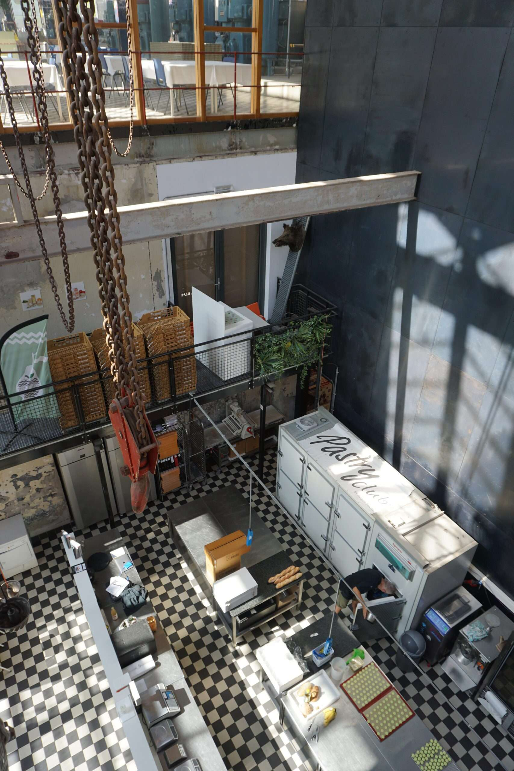 inside Pastry Club in Eindhoven, an industrial building with a pastry shop inside, with black and white tiled floor