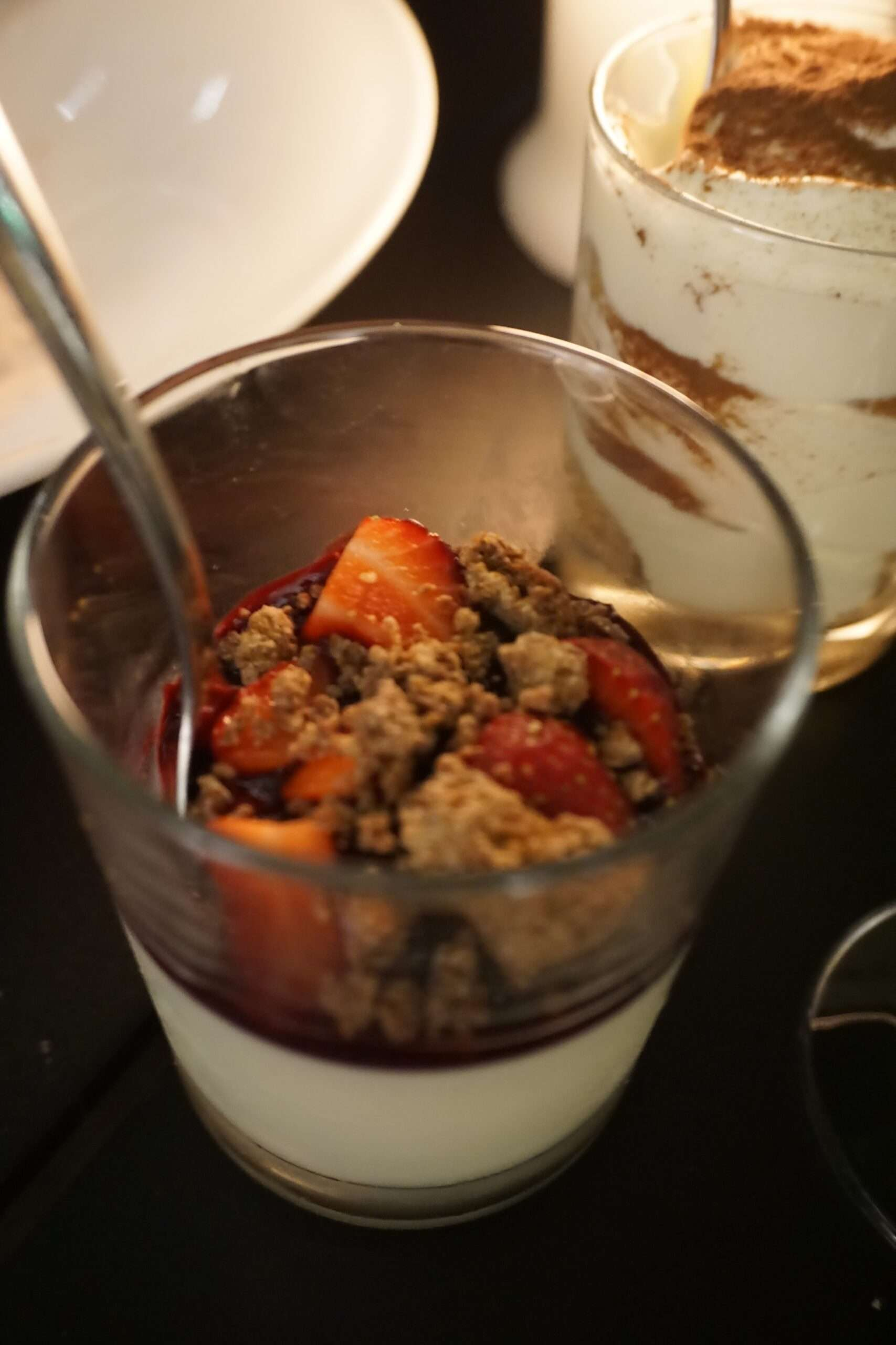 glass pot with dessert containing chocolate sauce, chopped strawberries and brown crumble at Kazerne restaurant