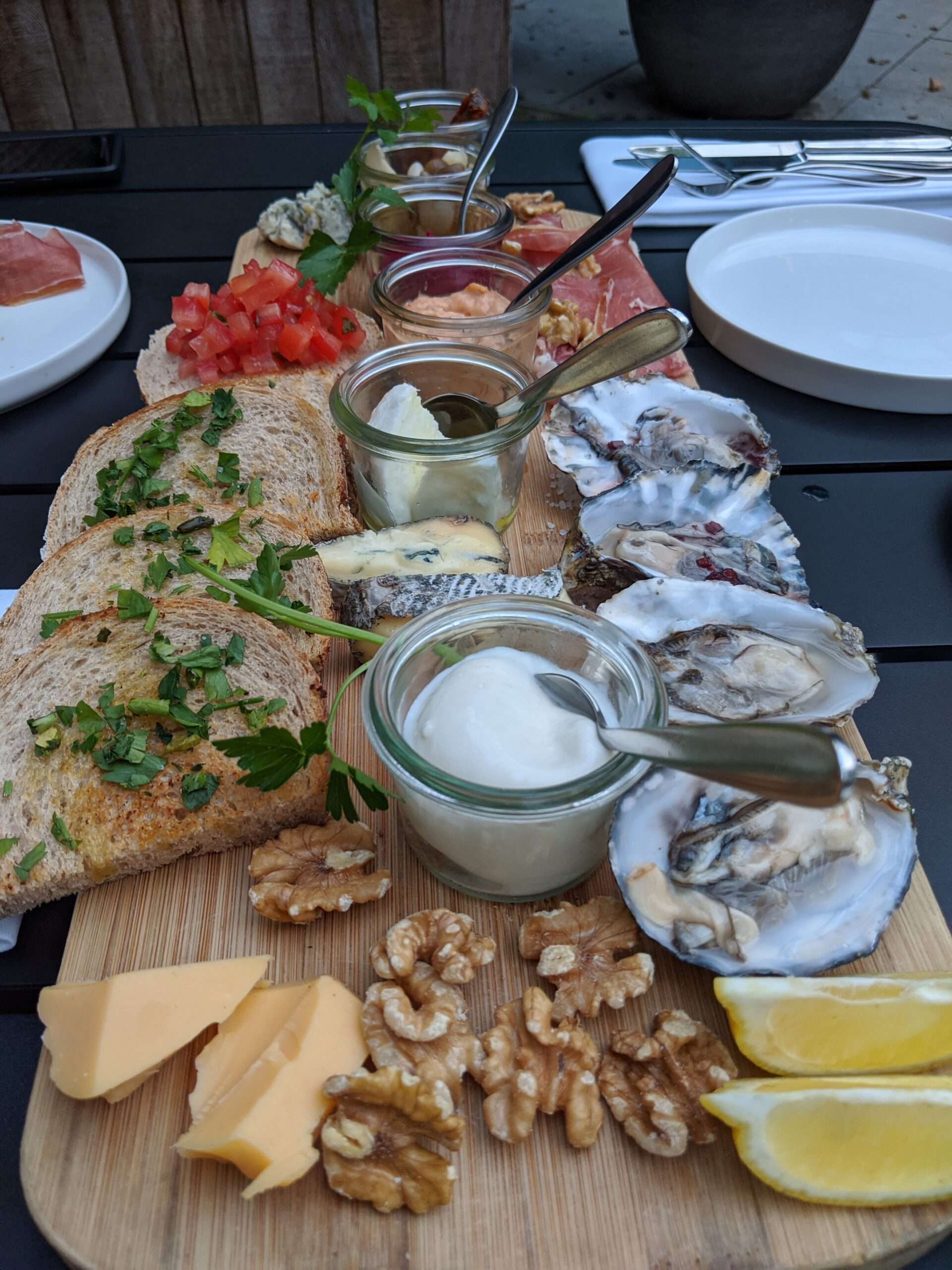 rectangular wooden platter with bruschetta topped with tomato and herbs, plus pieces of cheese, nuts, oysters and pot of sauce at Kazerne