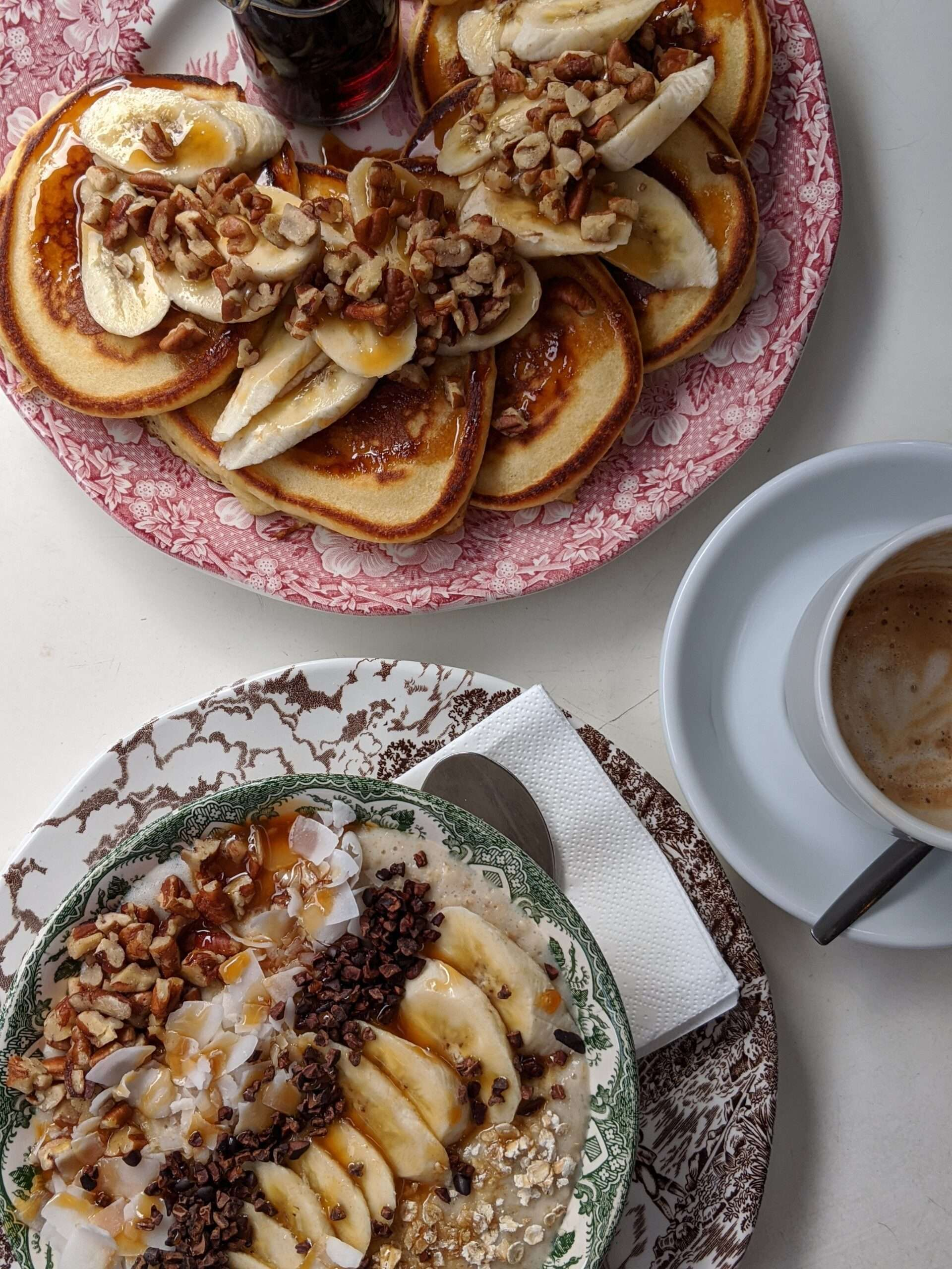 birdseye view of breakfast, pancakes with banana and chopped nuts, and oatmeal topped with fruit and nuts, plus a coffee in white cup and saucer