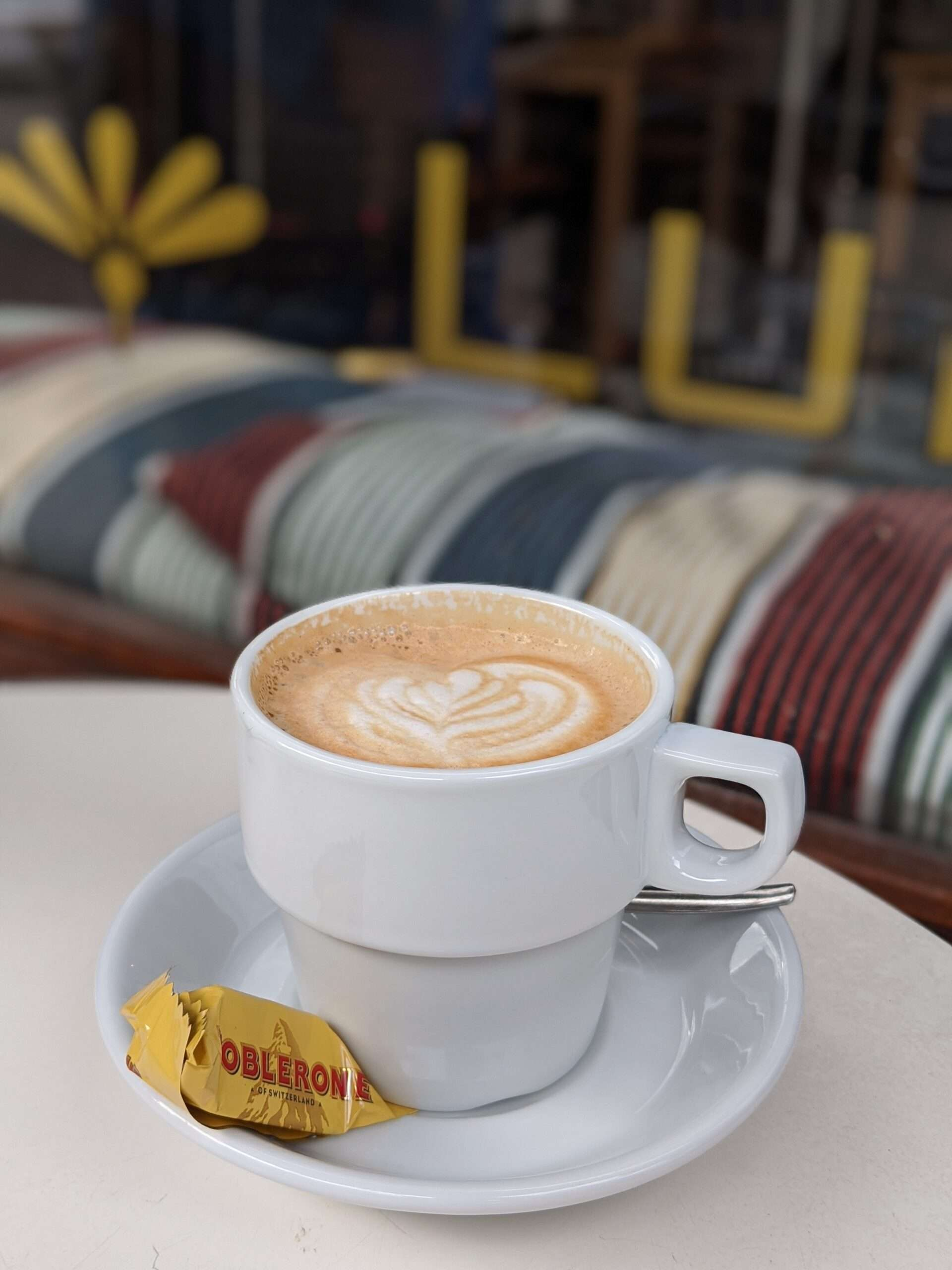 flat white coffee in a white cup and saucer, with a small toblerone chocolate on the side
