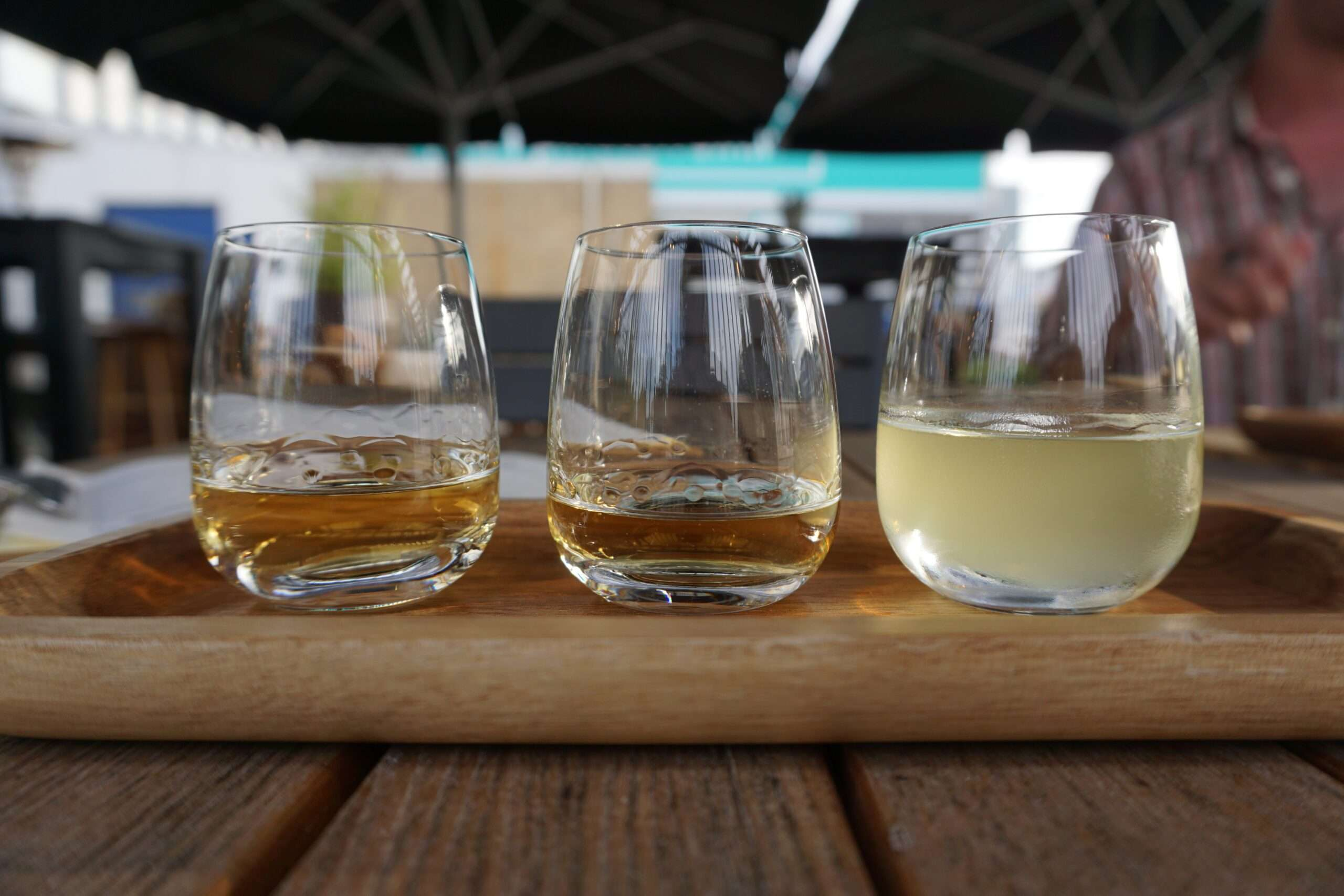 three tasting glasses of spirits on a wooden tray, two with whiskey and one with limoncello at Bottle Distillery Eindhoven