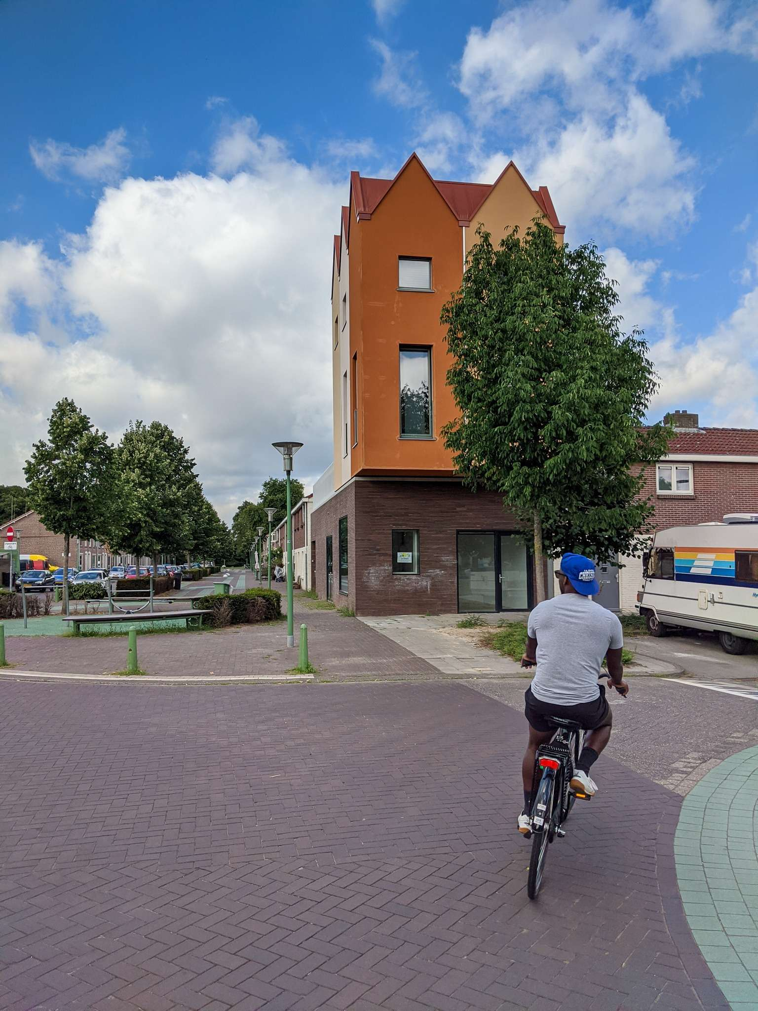 Man in grey t-shirt and blue hat cycles past an interesting orange house in Eindhoven