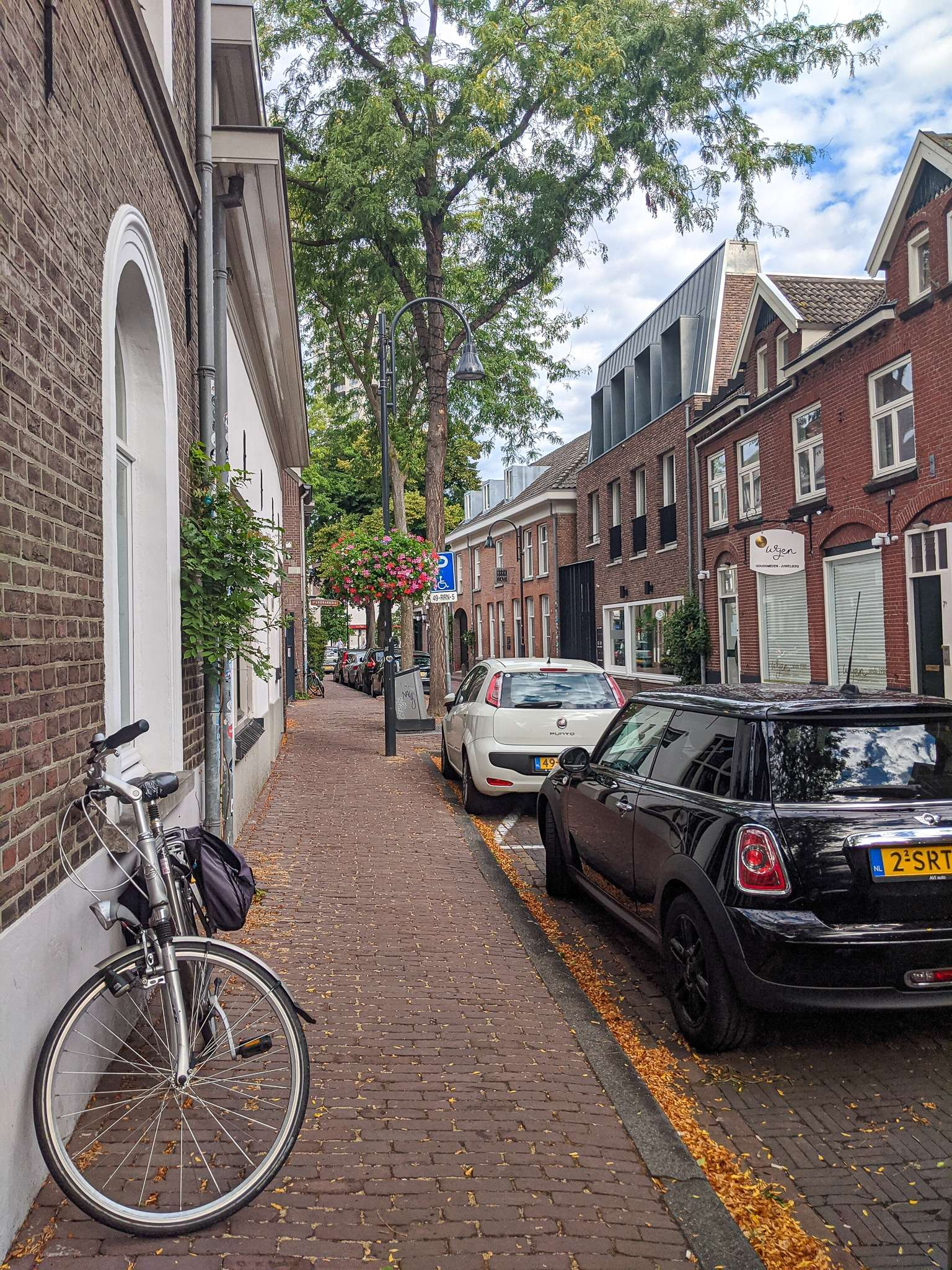 bicycle leaning against a red brick wall, with a black mini cooper parked beside it on a street in Eindhoven