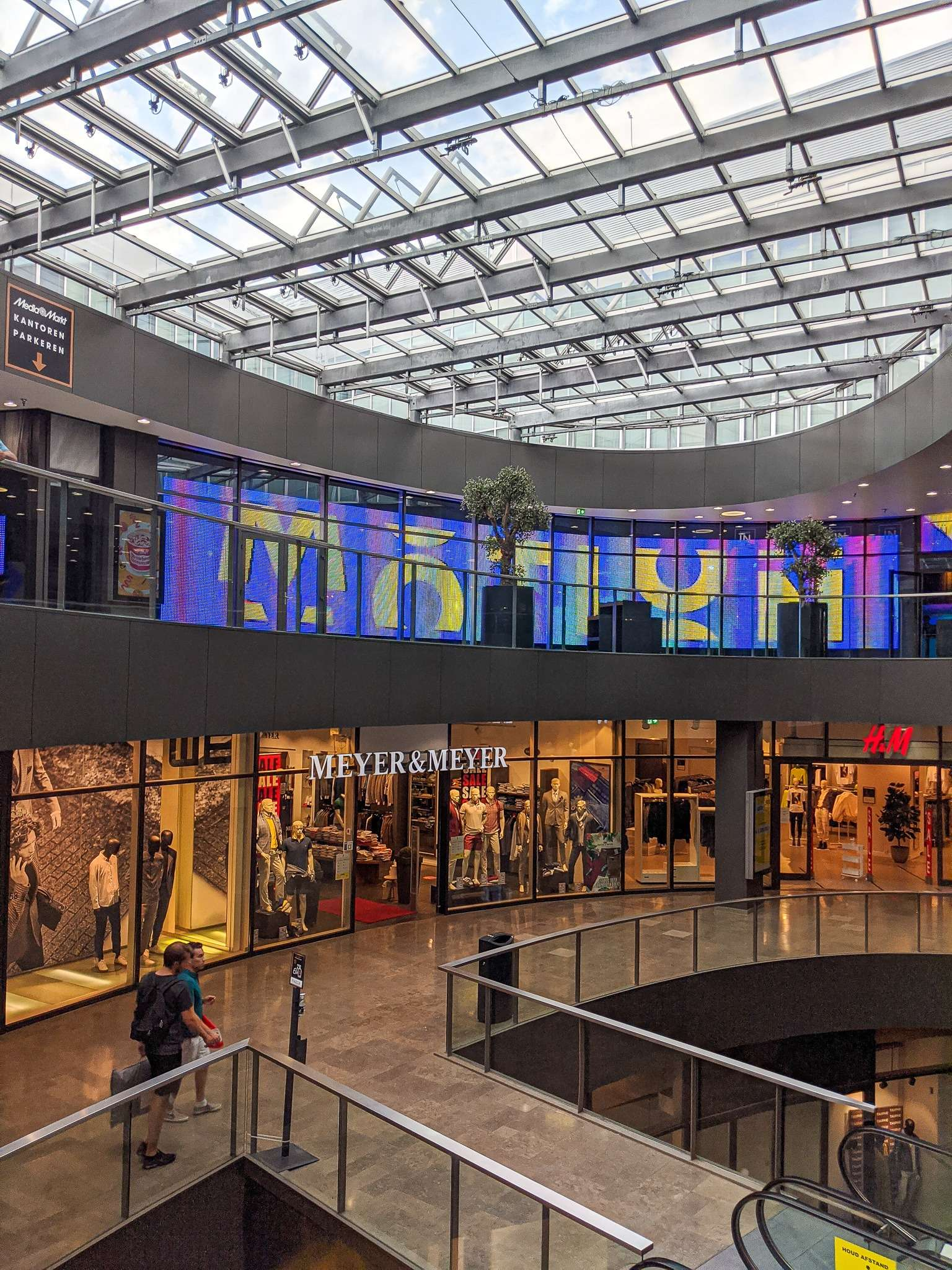 Inside a shopping mall in Eindhoven with glass roof and coloured lights inside the shops