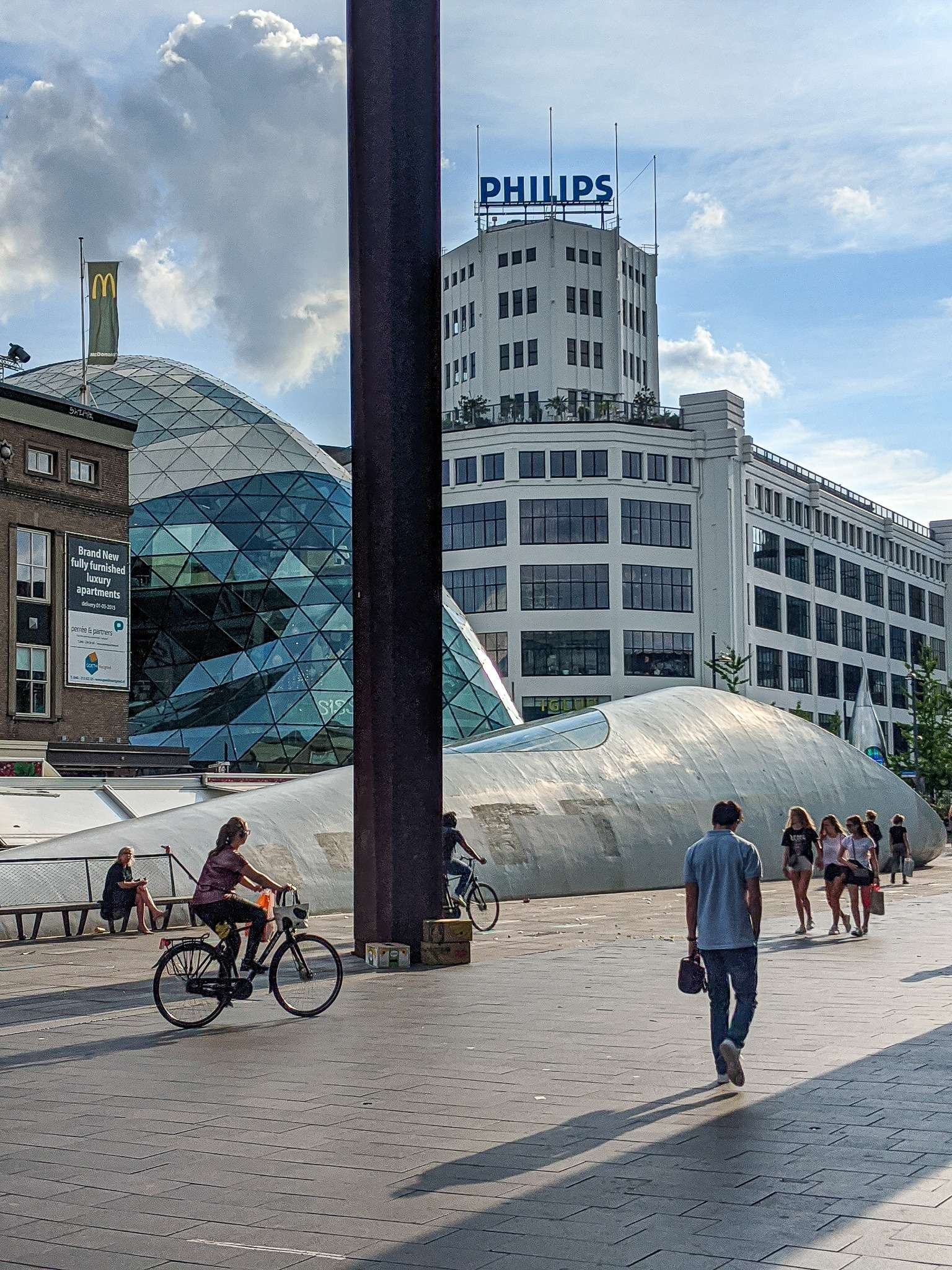 people walk and cycle in front of a Philips buildings and a modern glass building in Eindhoven city centre