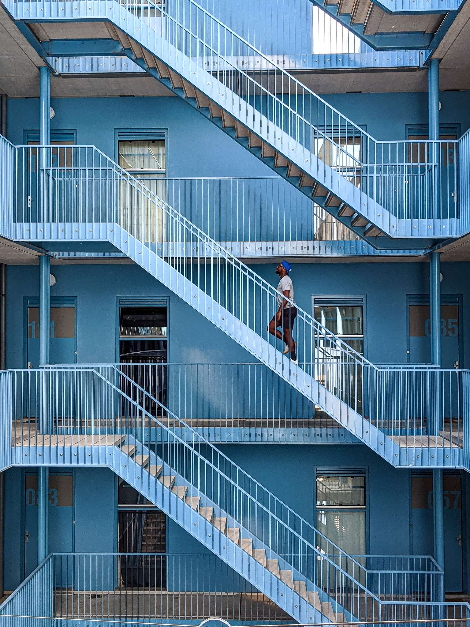 man in white t-shirt and black shorts walks up a set of blue metal stairs in the courtyard of an apartment block