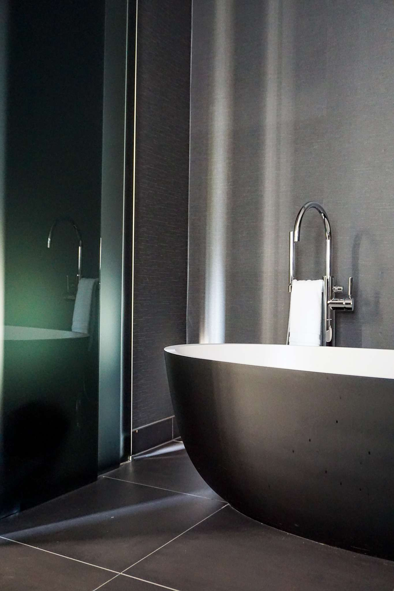 freestanding bathtub, black on the outside and white on the inside, next to a glass door at Kazerne hotel in Eindhoven