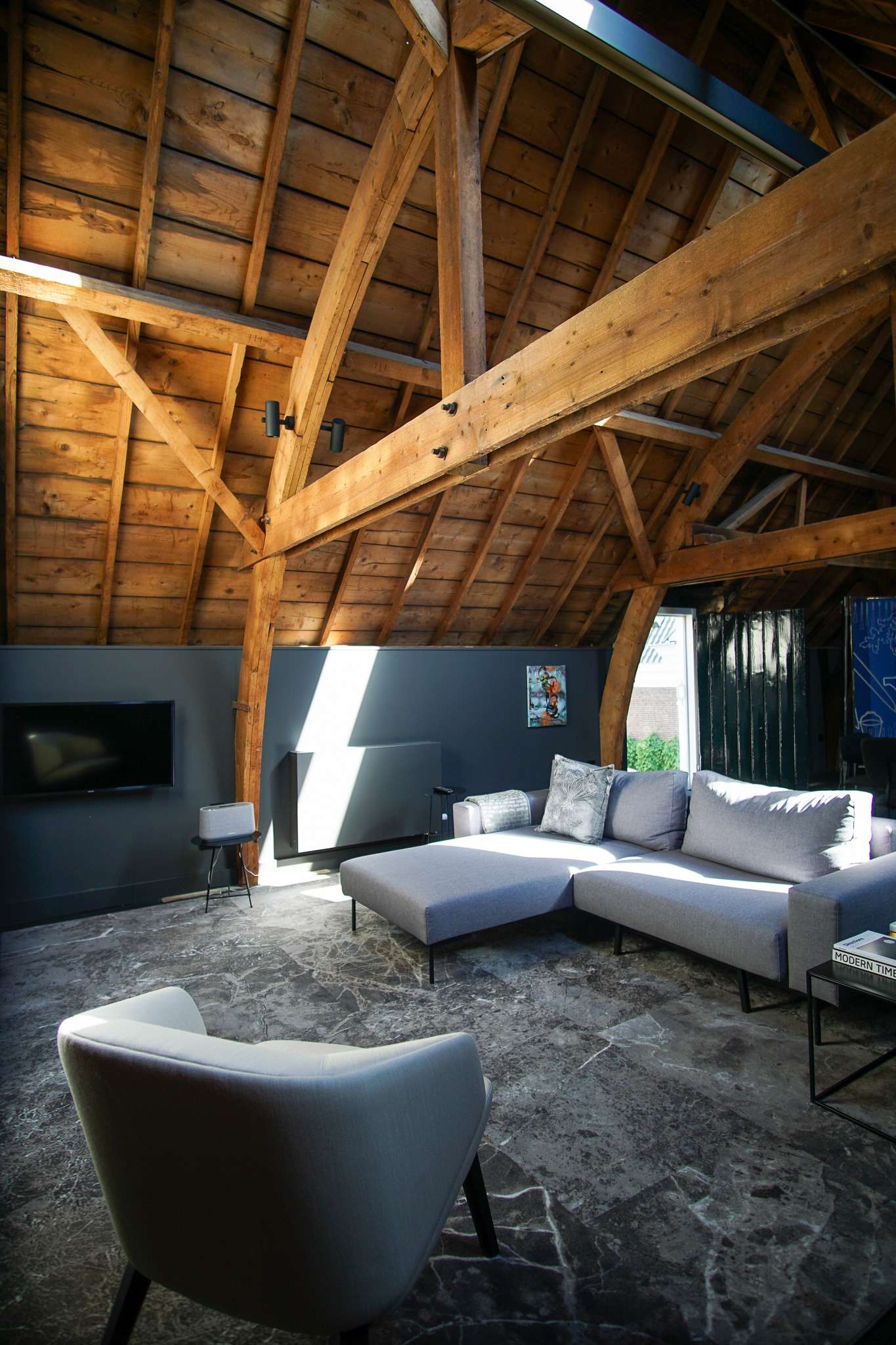 Wooden beams in a loft with large grey sofa at Kazerne Hotel in Eindhoven