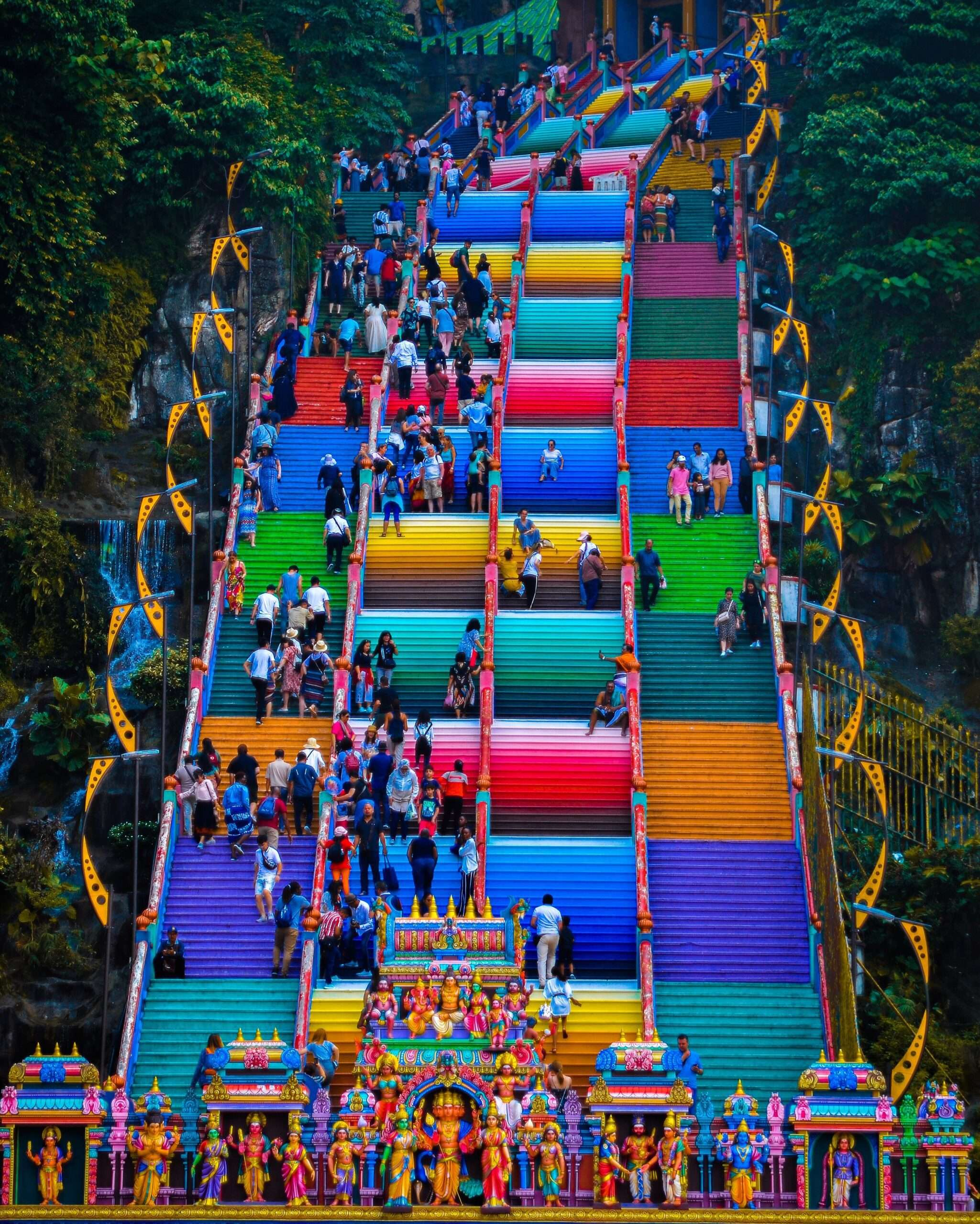 people walking up and down a brightly coloured tall staircase at Batu Caves Kuala Lumpur
