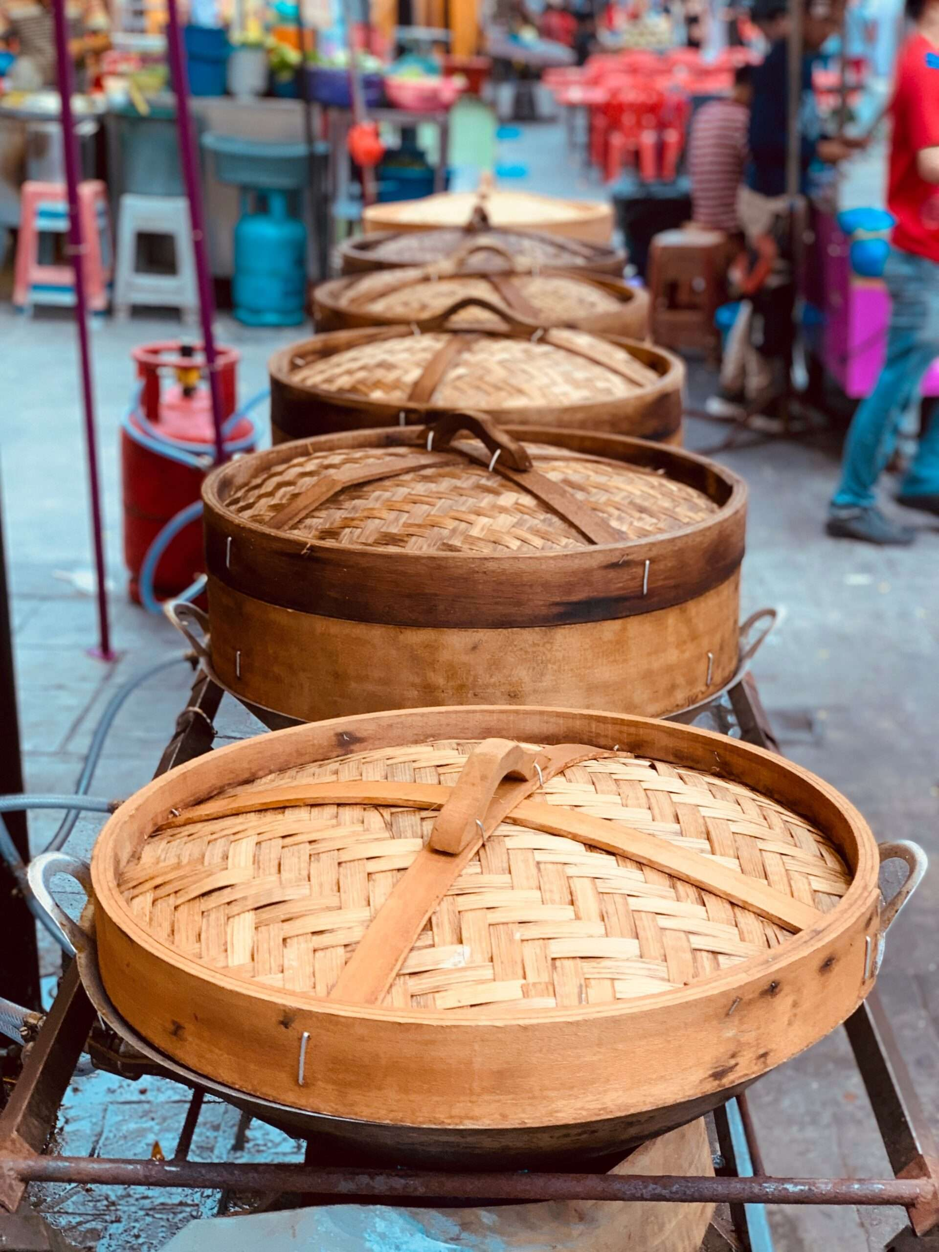 row of woven baskets containing food at a food market in Kuala Lumpur