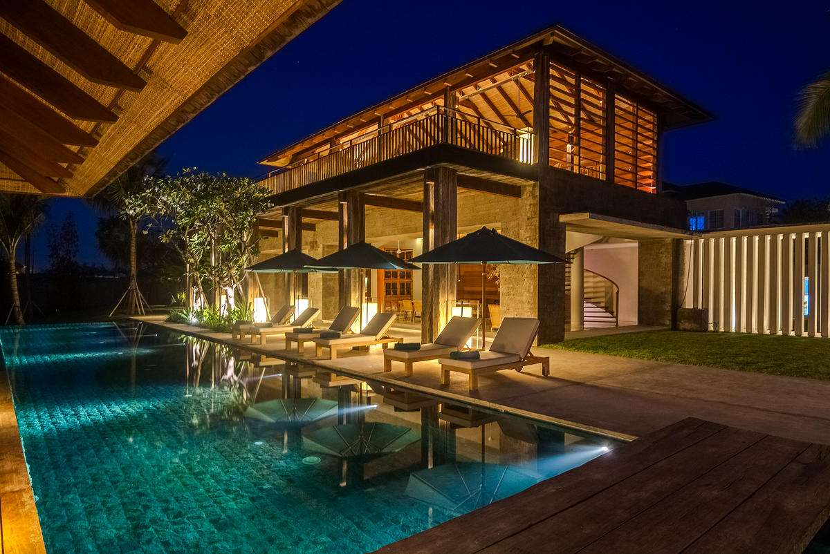 photo taken at night of the pool and villa, lit up with soft lighting, at Ambalama Bali, one of the top villas in the world