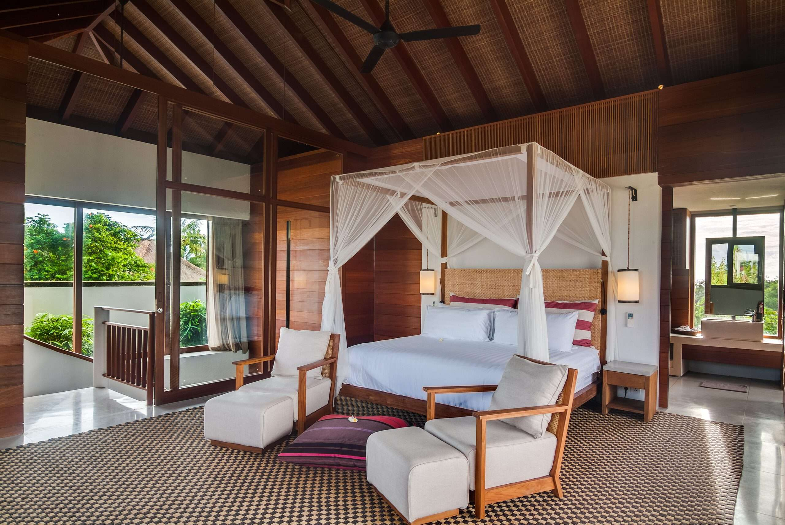 4 poster bed with two armchairs at the end, in a spacious bedroom at Ambalama Bali, one of the top villas in the world