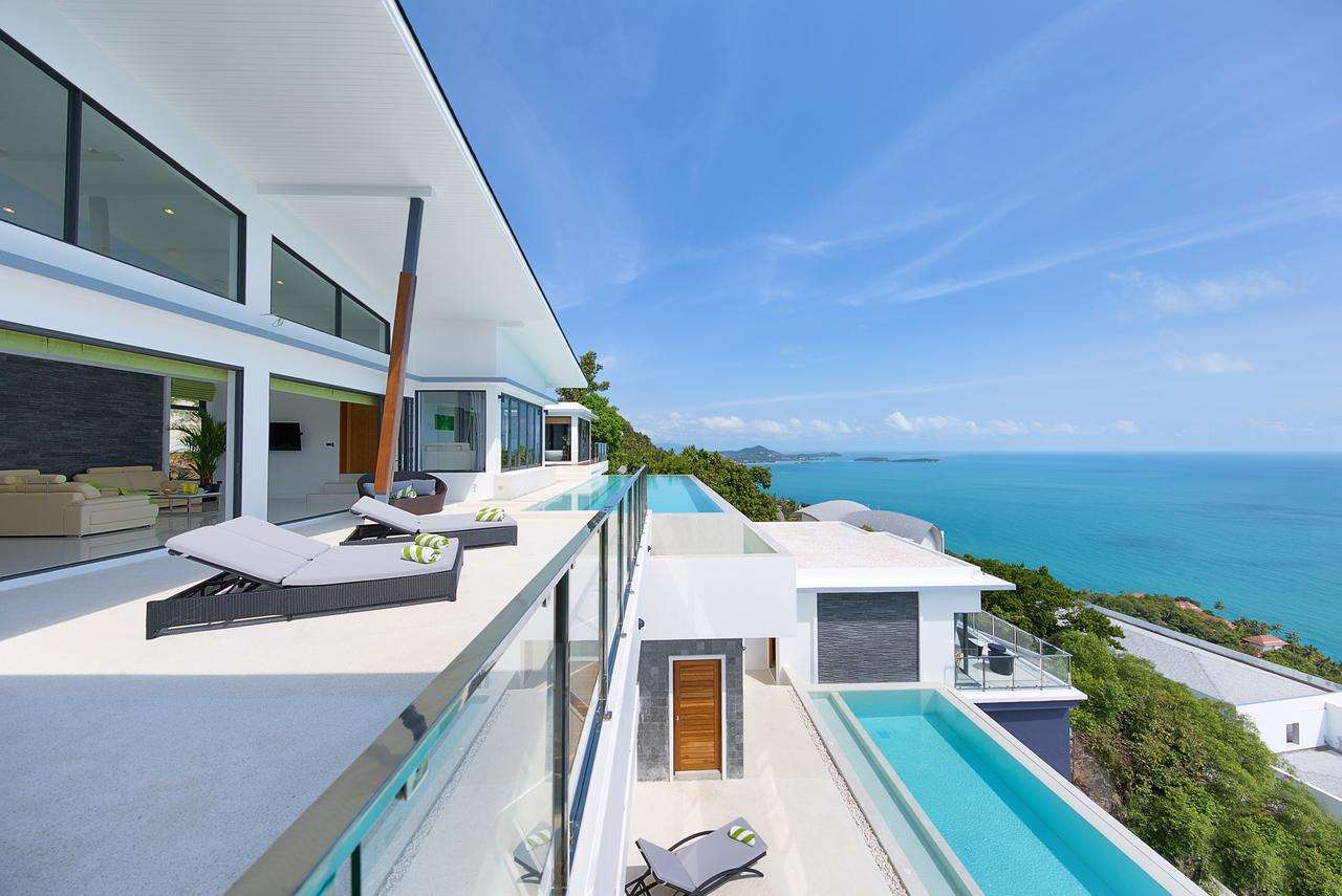side view of the villa, infinity pools and sun loungers overlooking the sea at Karpe Diem, one of the top villas in the world