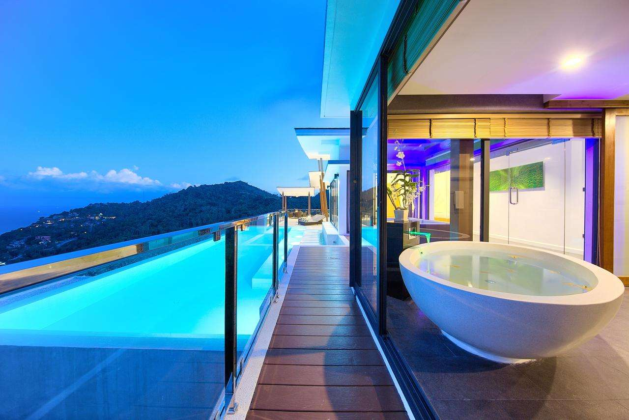 side view of white freestanding bathtub and turquoise infinity pool at night, at Karpe Diem, one of the top villas in the world