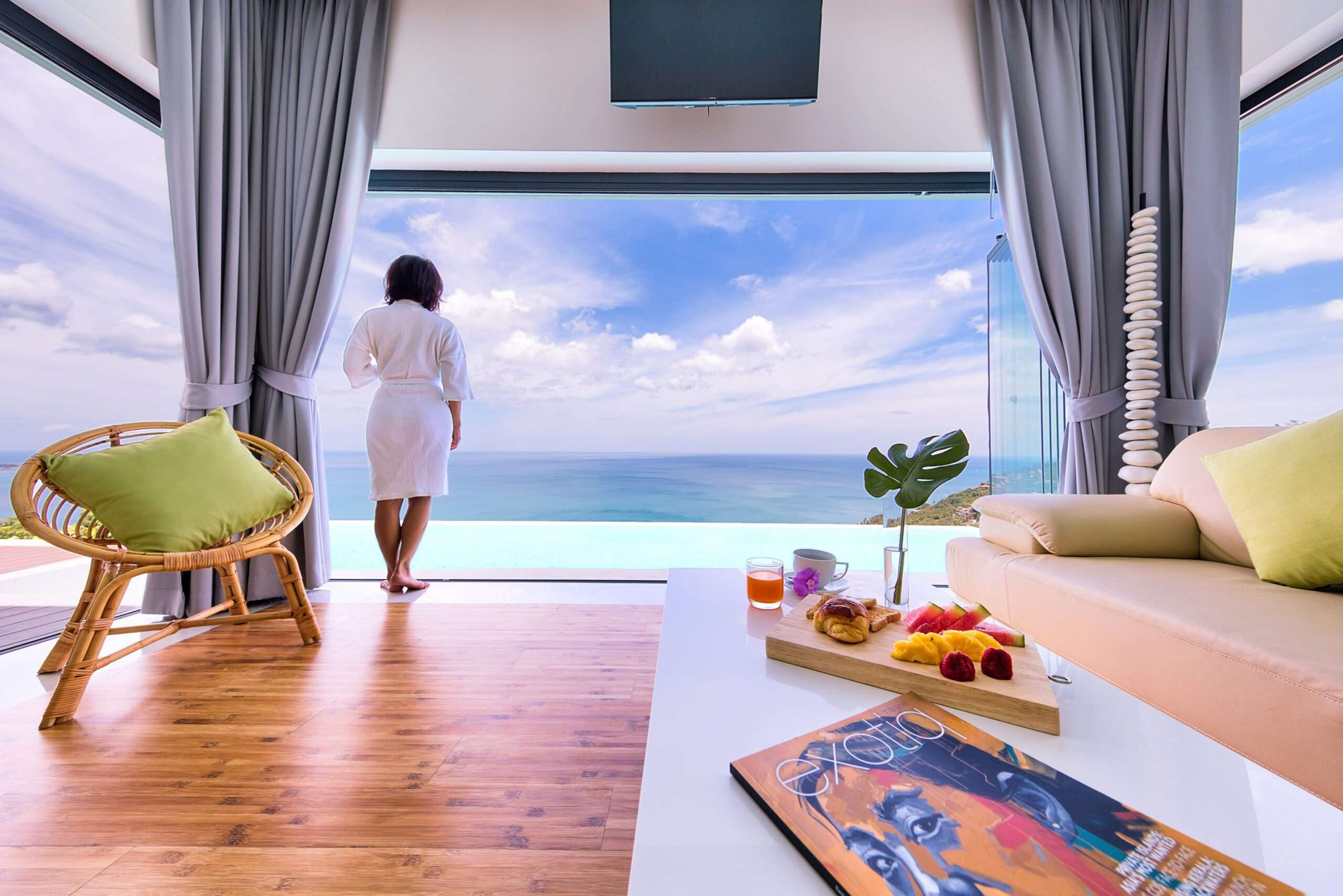 lady in white robe looks at the view of the pool and ocean from Karpe Diem, top villas in the world
