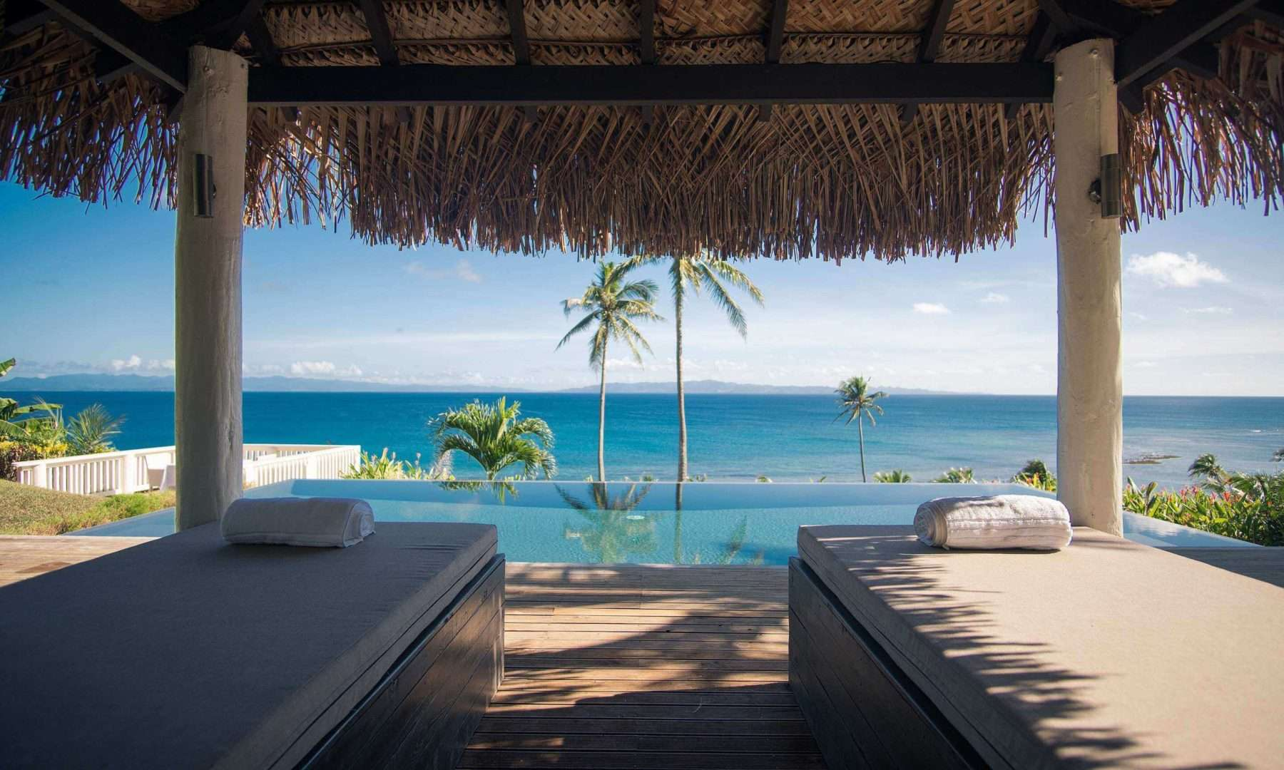 sun loungers by the infinity pool overlooking the sea at Raiwasa Resort Fiji