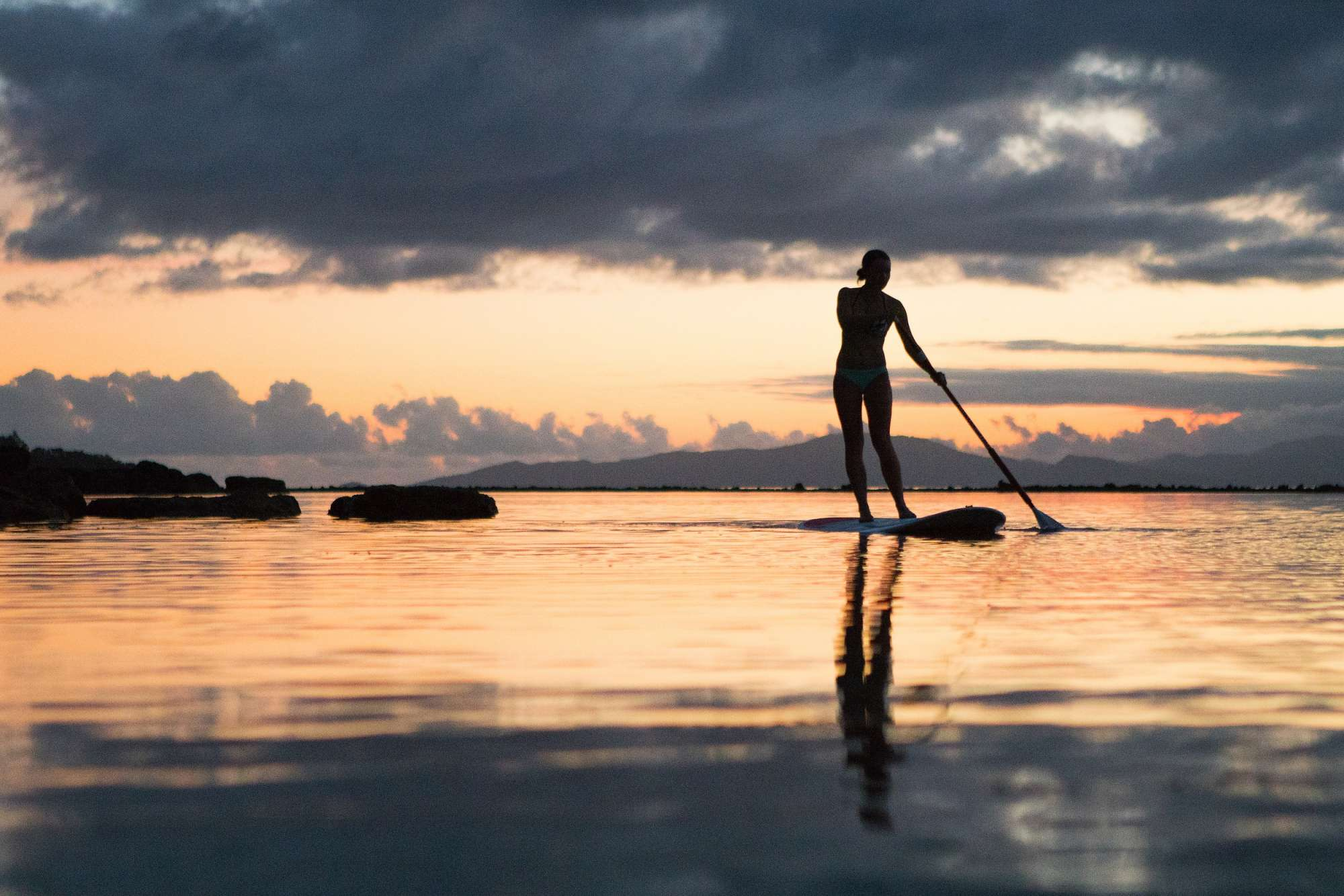 lady stand up paddle boarding in the sea at sunset, at Raiwasa Resort Fiji