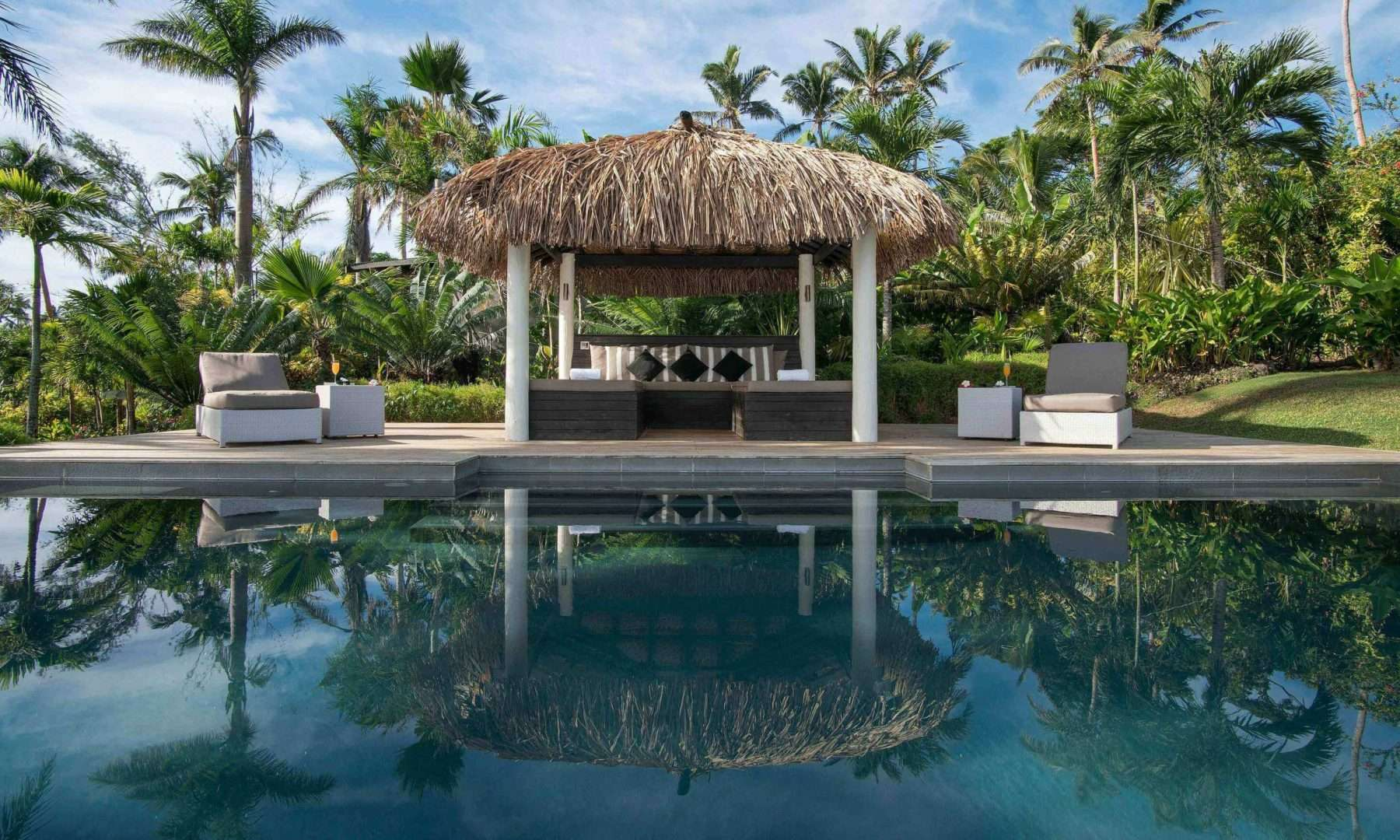 swimming pool surrounded by palm trees at Raiwasa Resort Fiji