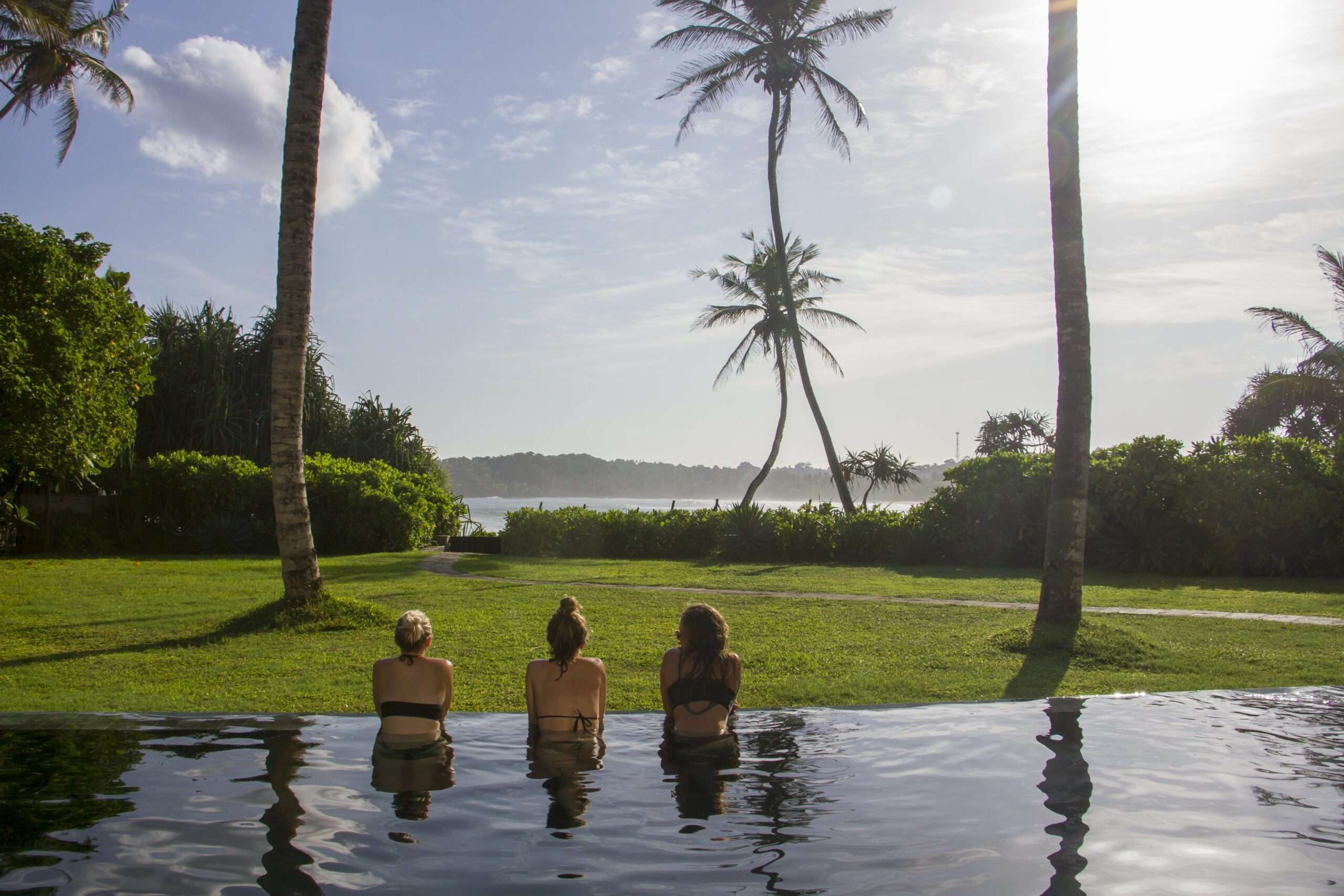 Three women sit in the swimming pool at Talalla House in Sri Lanka