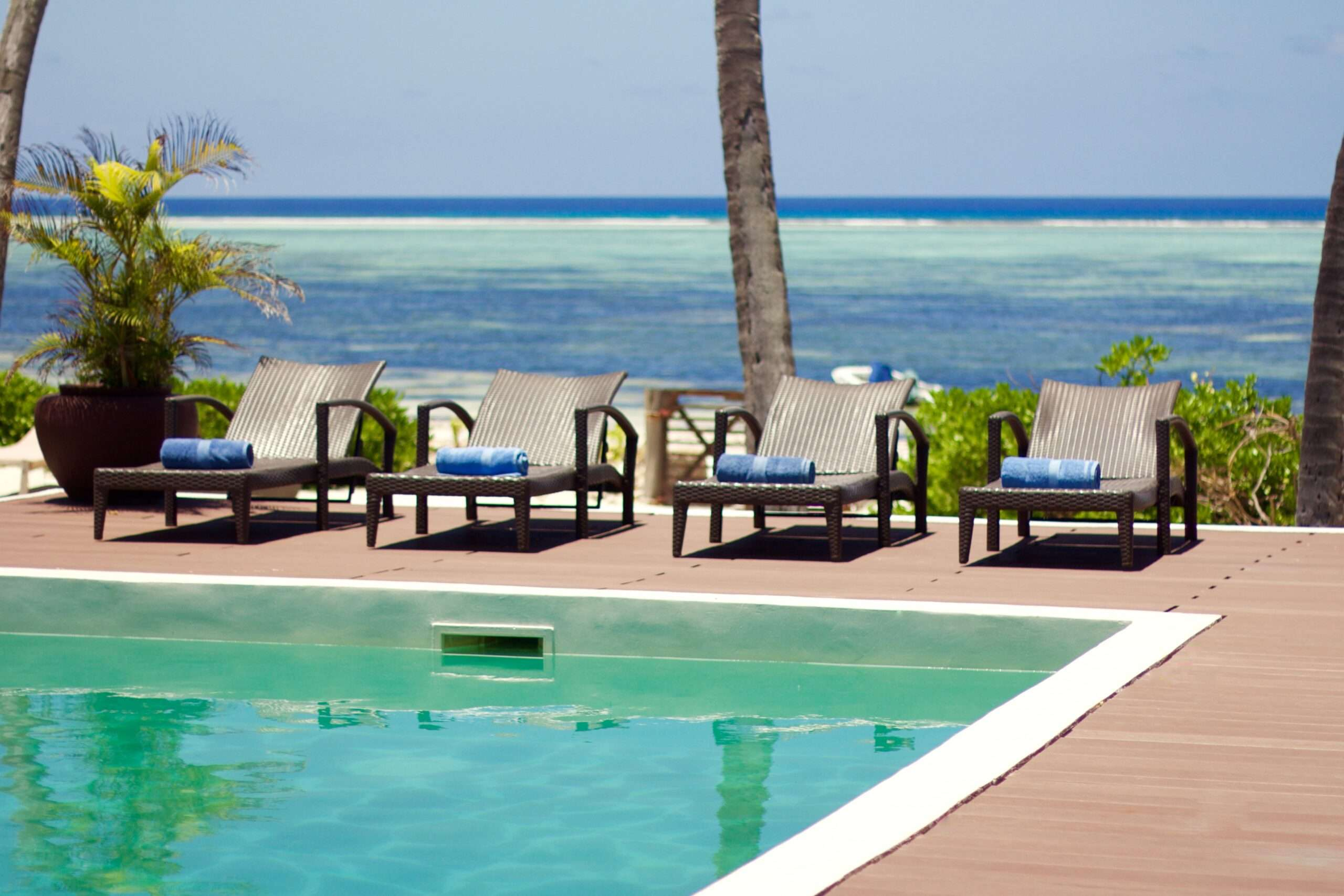 swimming pool with loungers and a sea view at Turquoise Beach Villa Zanzibar