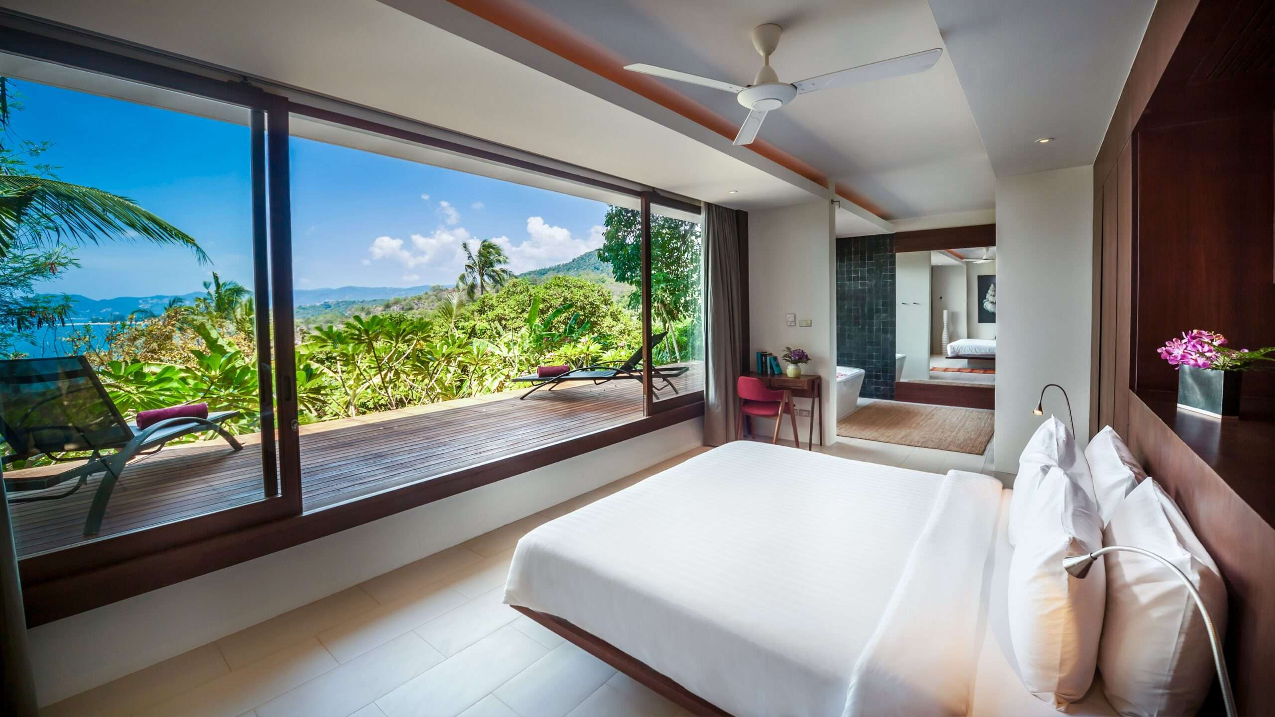 large bedroom with glass wall leading to a balcony overlooking the sea at Villa Hin Koh Samui