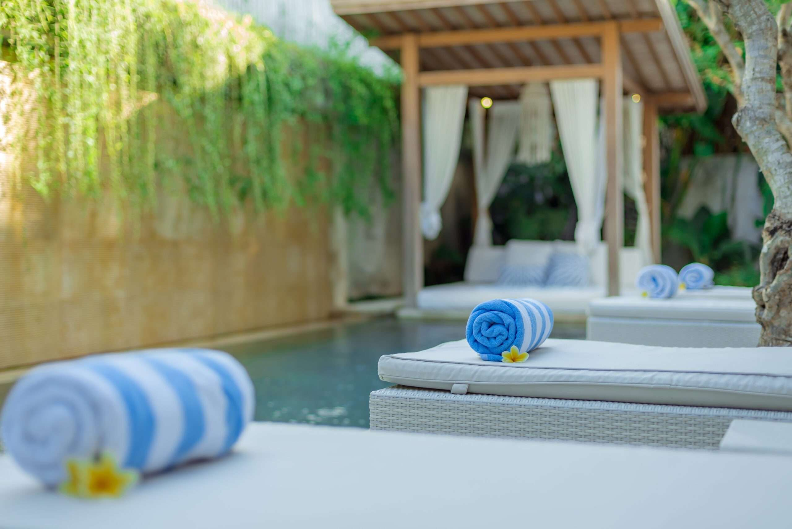 Sun lounge chairs and towels next to pool at Villa Savasana in Bali