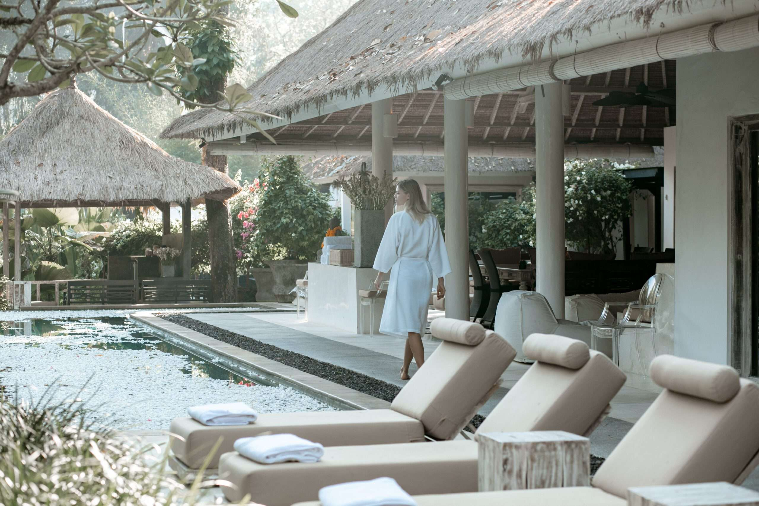 lady wearing a white bathrobe walks beside the pool filled with petals at Villa Sungai Bali
