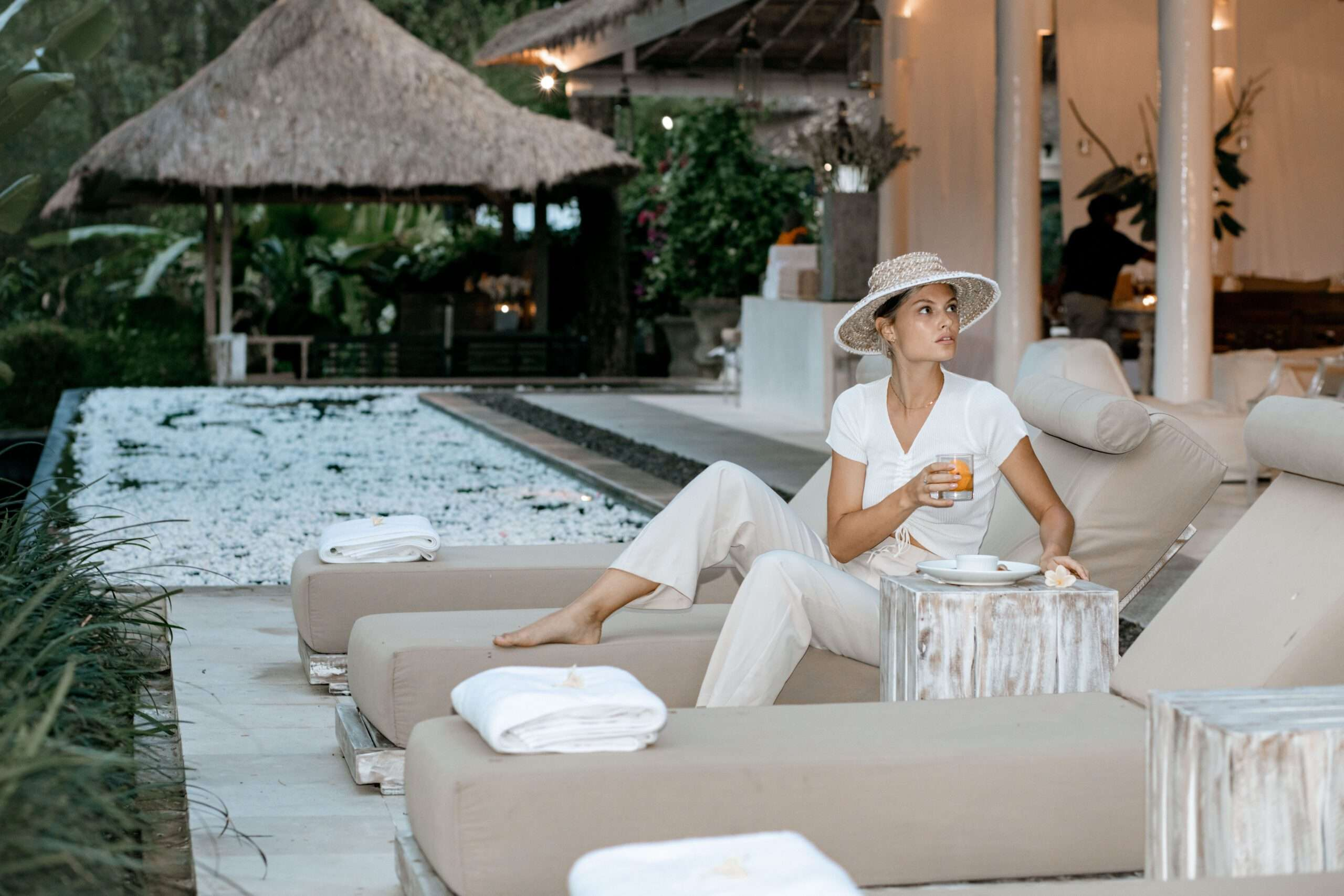 lady wearing white enjoys a drink on a sun lounger at Villa Sungai Bali