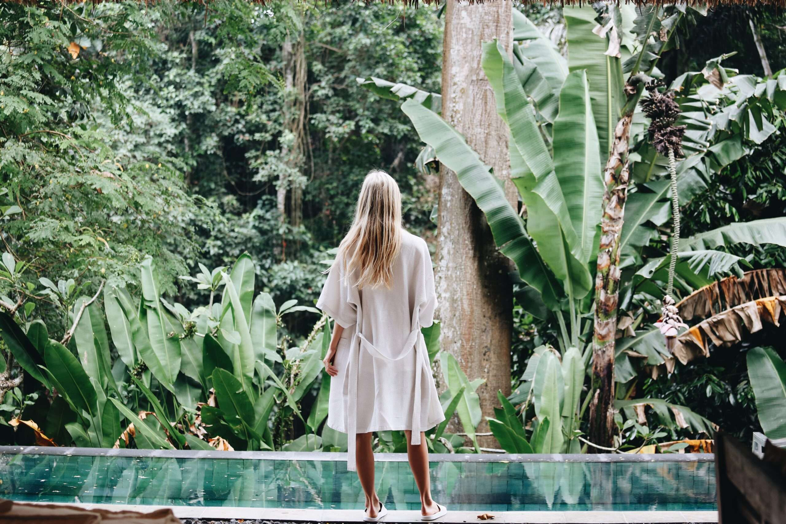 lady in a white bathrobe stands by a swimming pool looking out to the jungle at Villa Sungai Bali