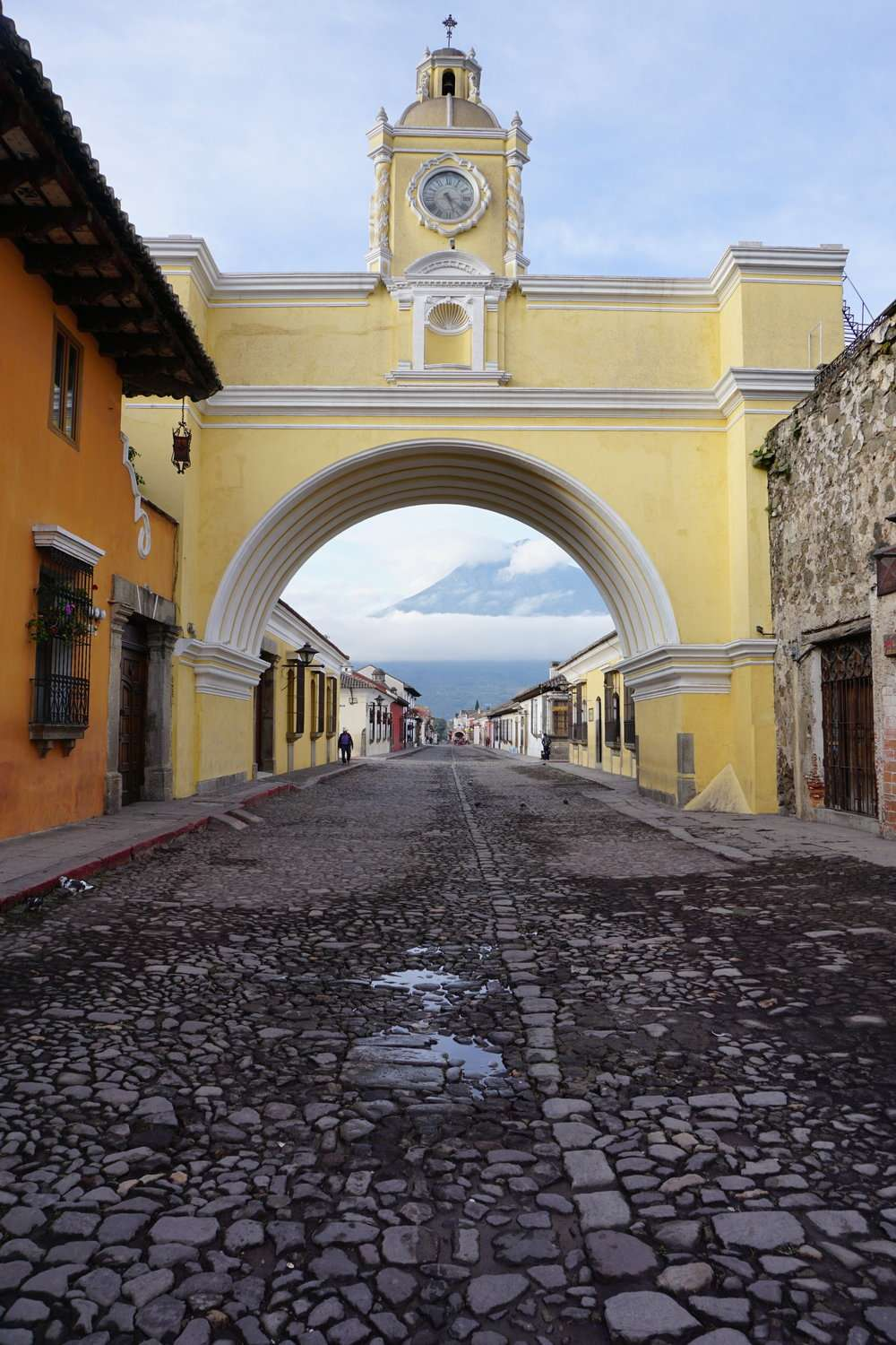 large yellow archway over a cobbled street in Antigua, with view of a volcano under the arch
