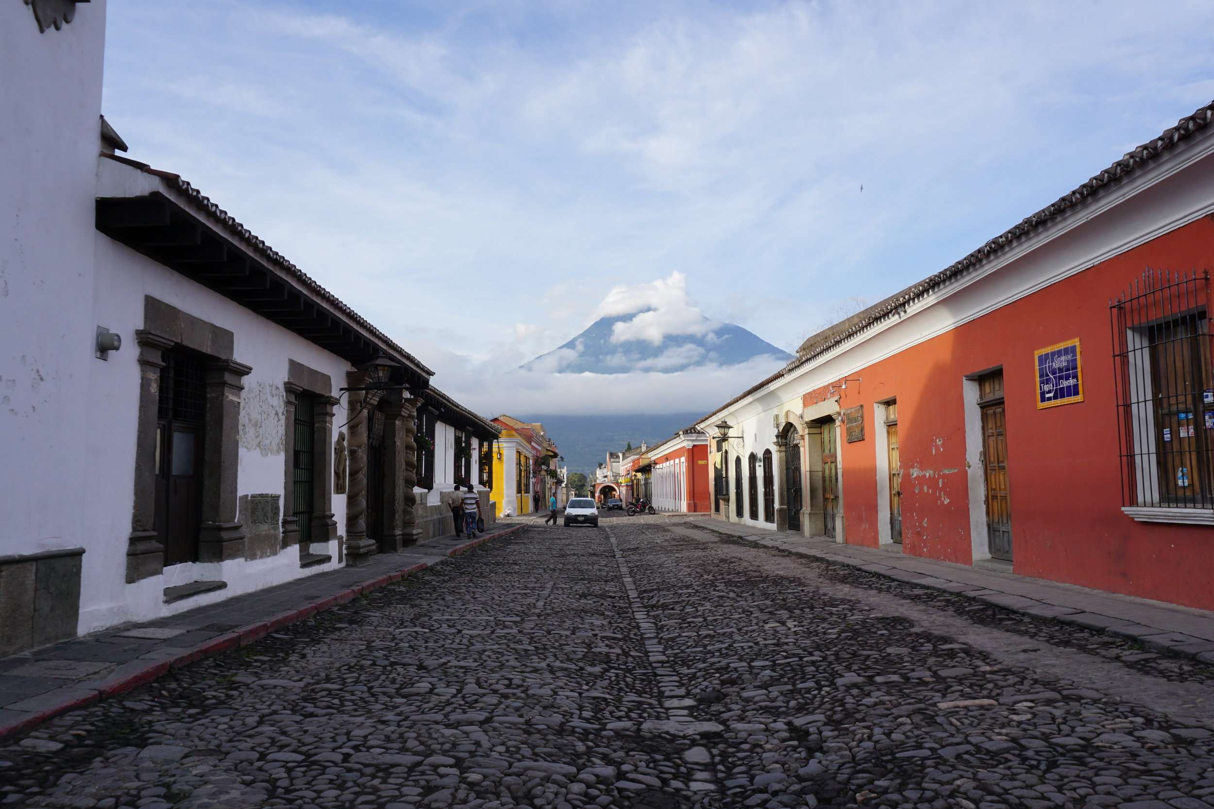 a cobbled street with colourful buildings, with a large volcano at the end, in Antigua, Guatemala